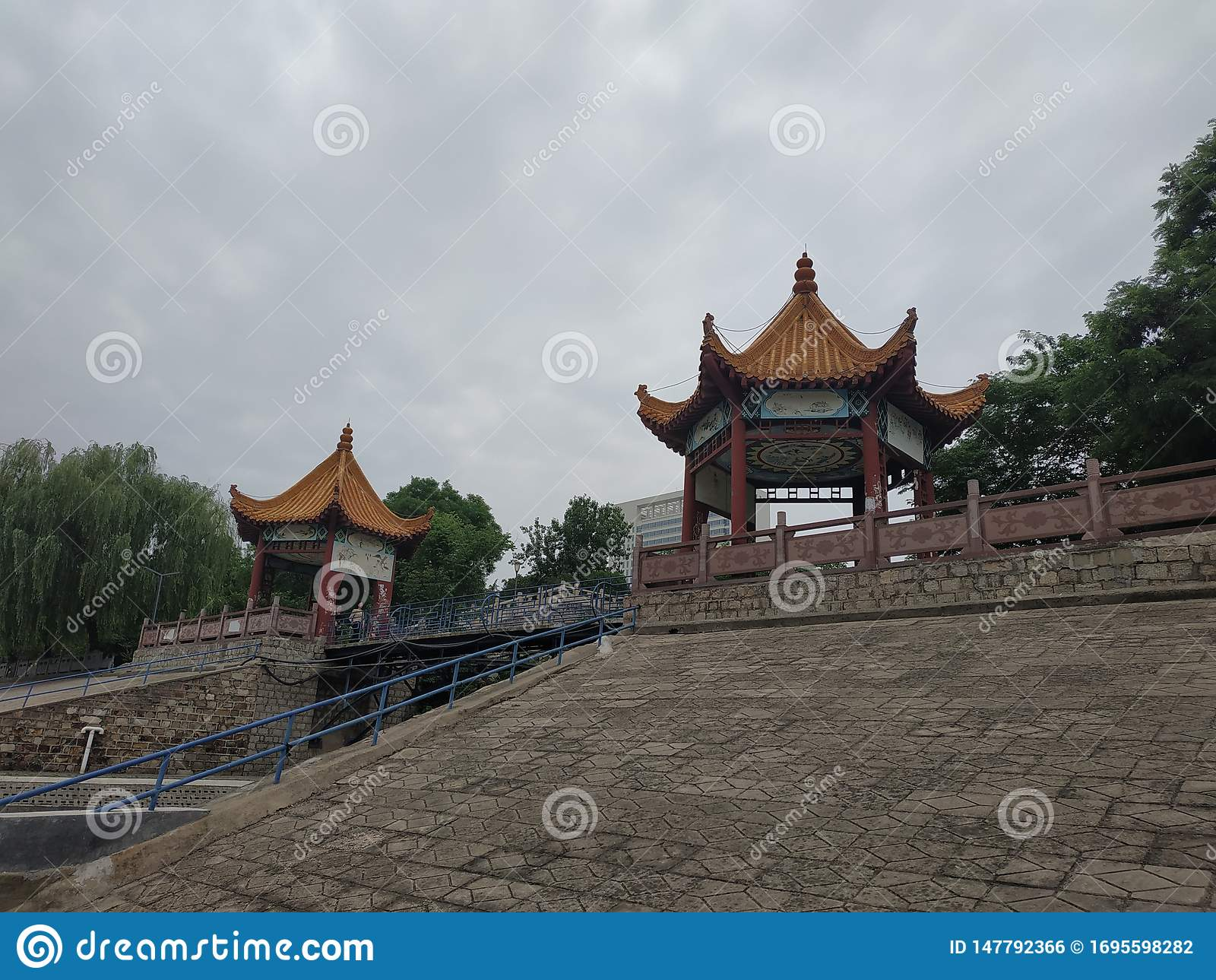 Há dois pavilhões no banco do rio no parque