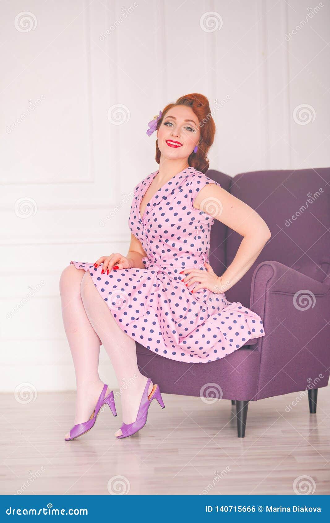 Hübscher redheaded Stift herauf die Frau, die rosa Tupfenkleid trägt und mit purpurrotem Lehnsessel auf weißem Hintergrund aufwir