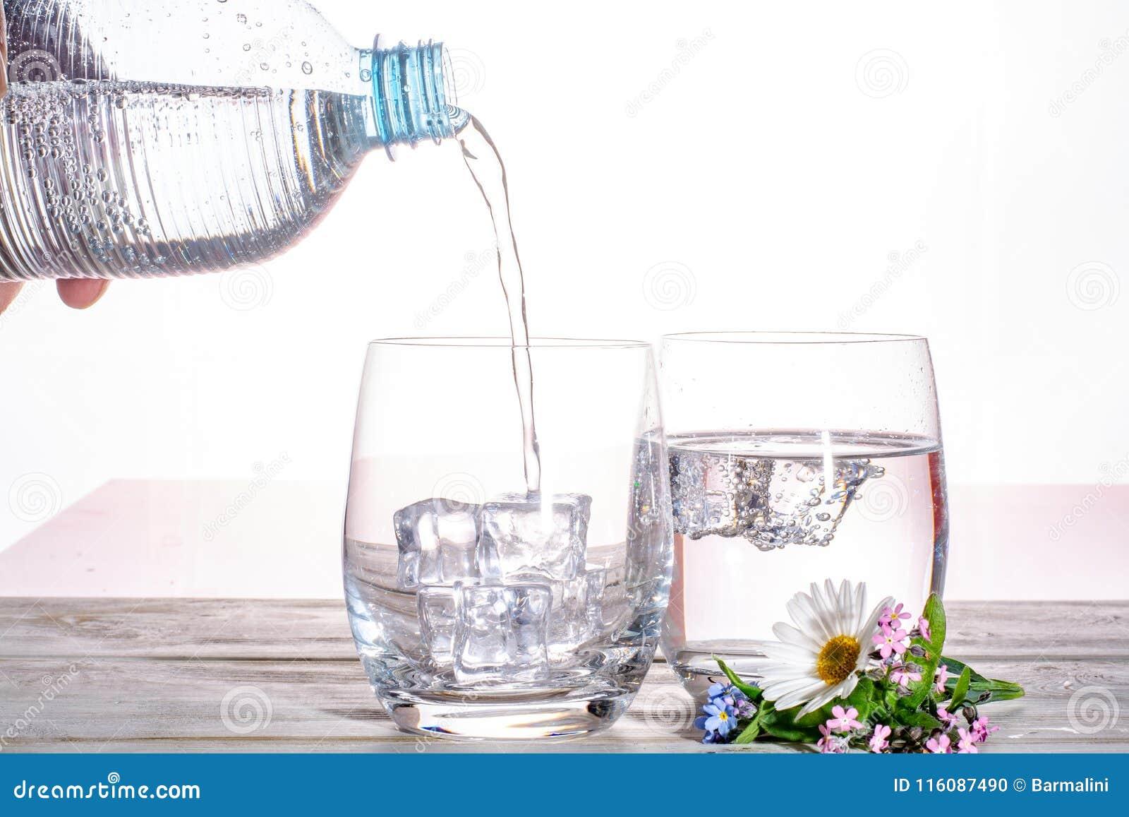 Hälla av mineraliskt drinkvatten för mousserande sodavatten i exponeringsglas med ic