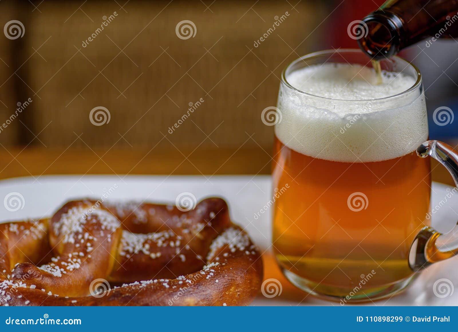 Hällande öl in i ett stort exponeringsglas rånar på plattan med varm mjuk pret