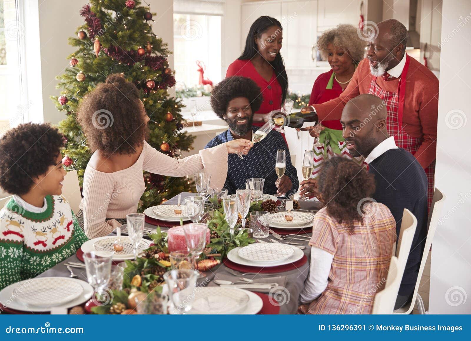Hällande champagne för farfar på matställetabellen under en mång- utveckling, för familjjul för blandat lopp beröm