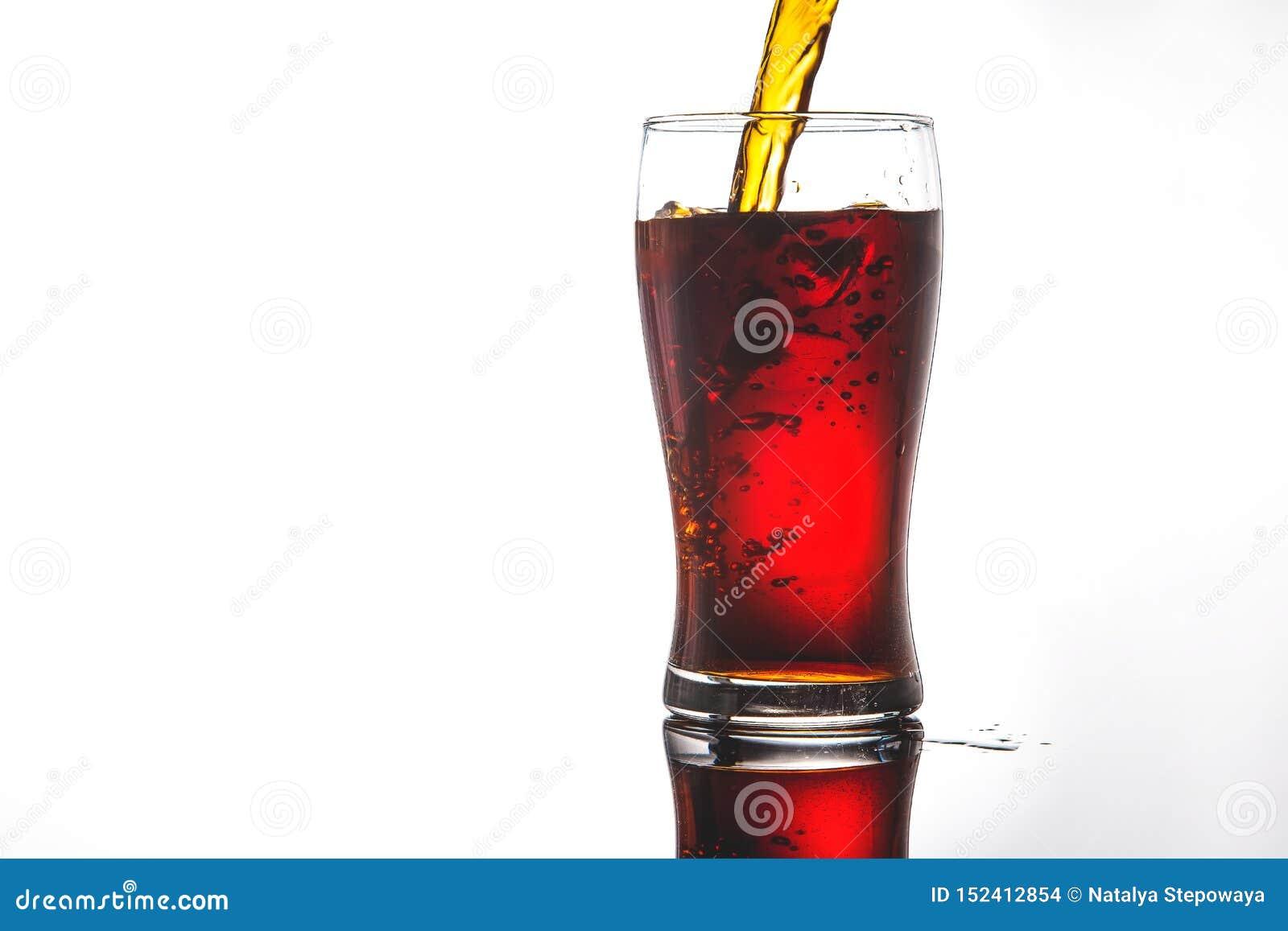 Hällande cola in i exponeringsglas med is på vitt bakgrundskopieringsutrymme