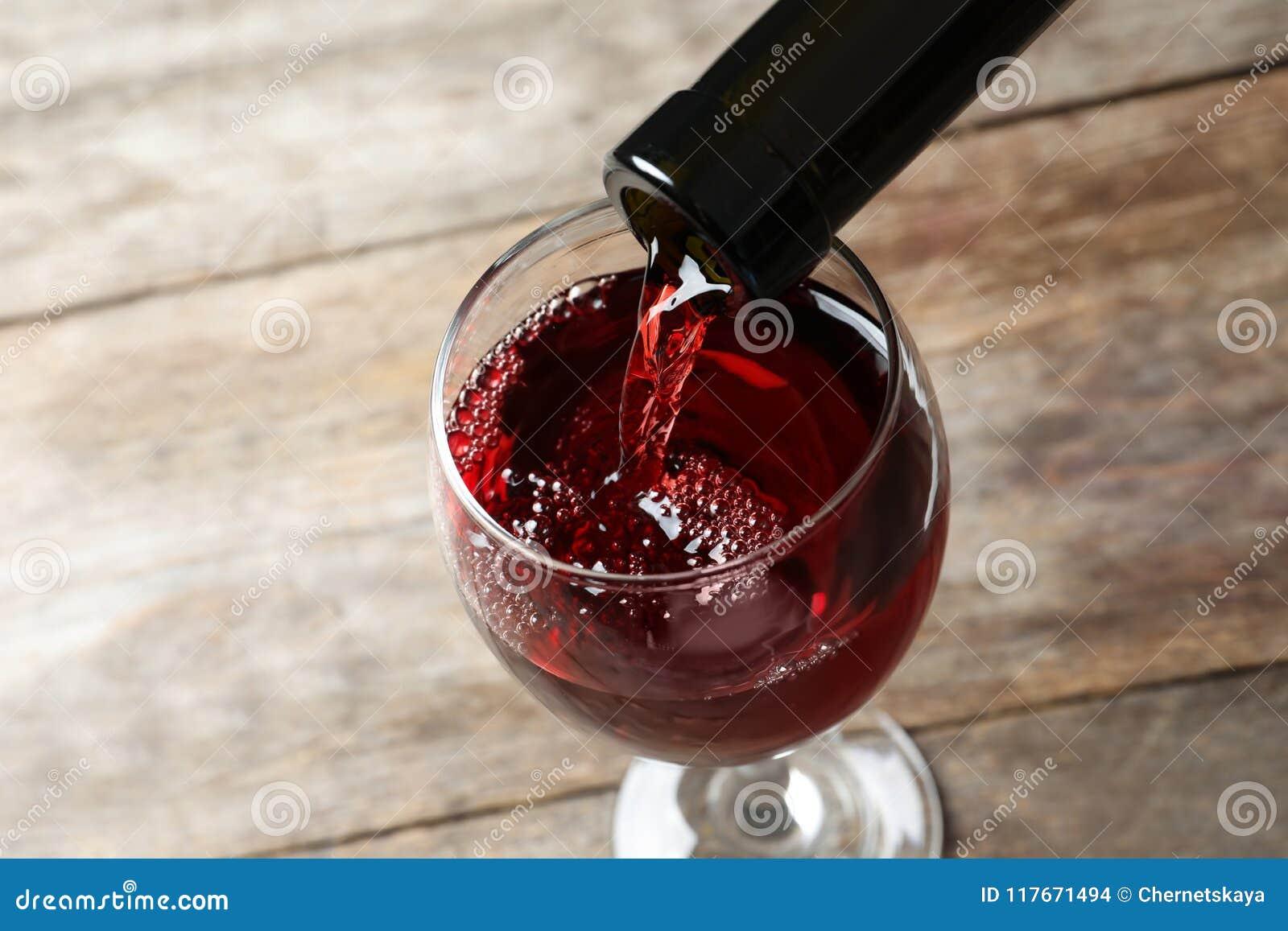 Hällande läckert rött vin in i exponeringsglas