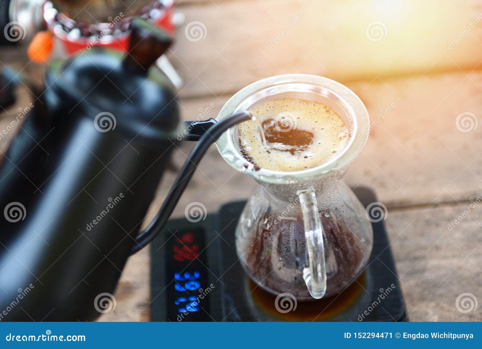 Hällande vatten för droppandekaffebarista på filtrerat brygga - som gör kaffe för kopphanddroppande i exponeringsglaskrus på vägn