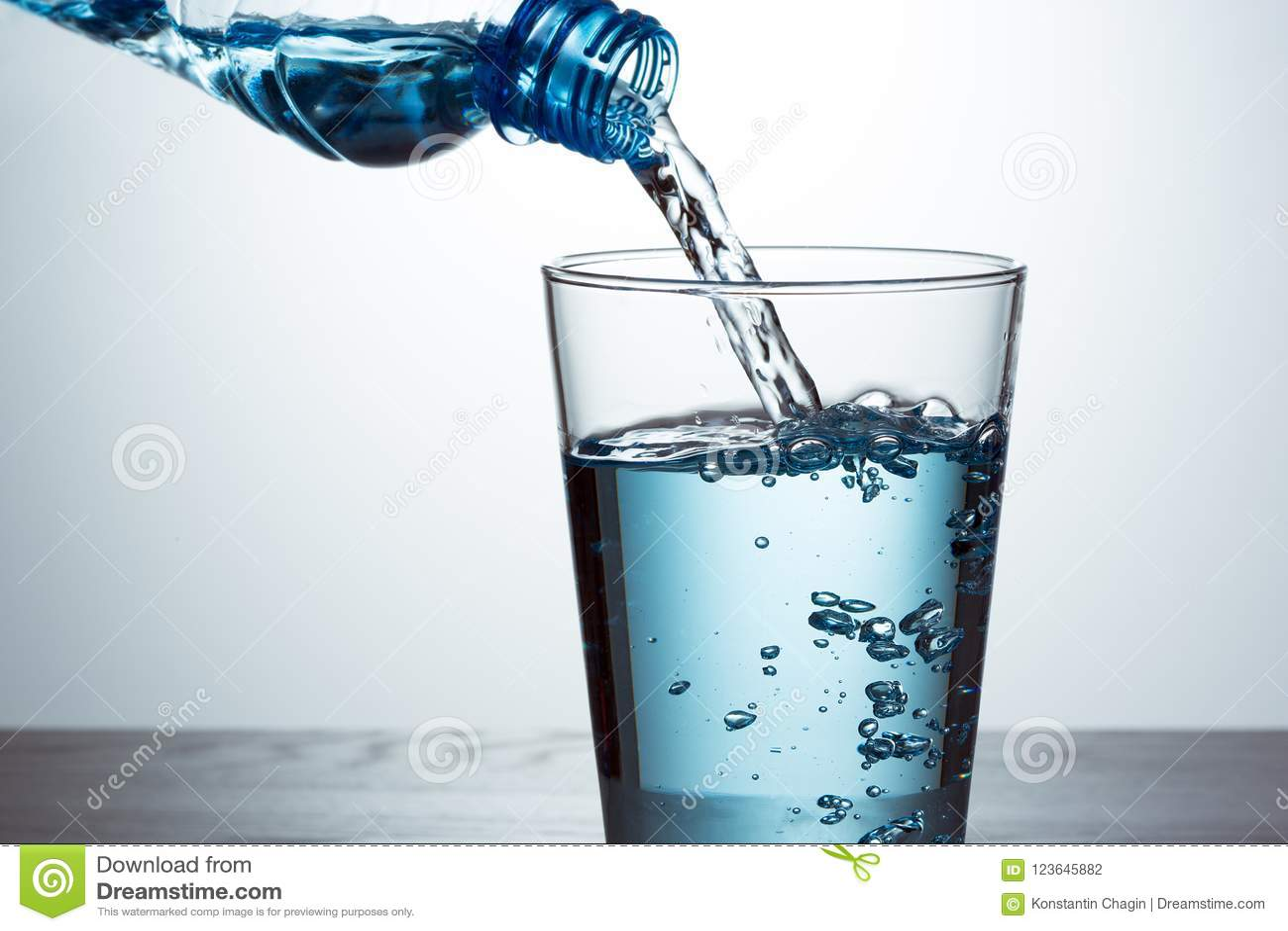 Hällande vatten från flaskan in i exponeringsglas