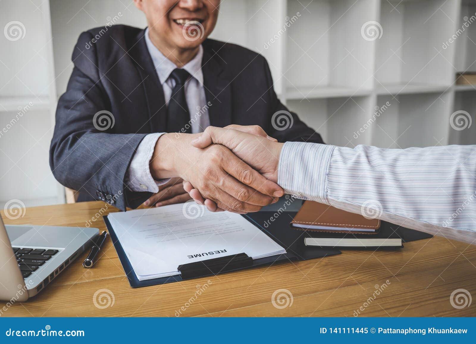 Hälsa nya kollegor, handskakningen medan jobb som intervjuar, den manliga kandidaten som skakar händer med intervjuaren eller arb