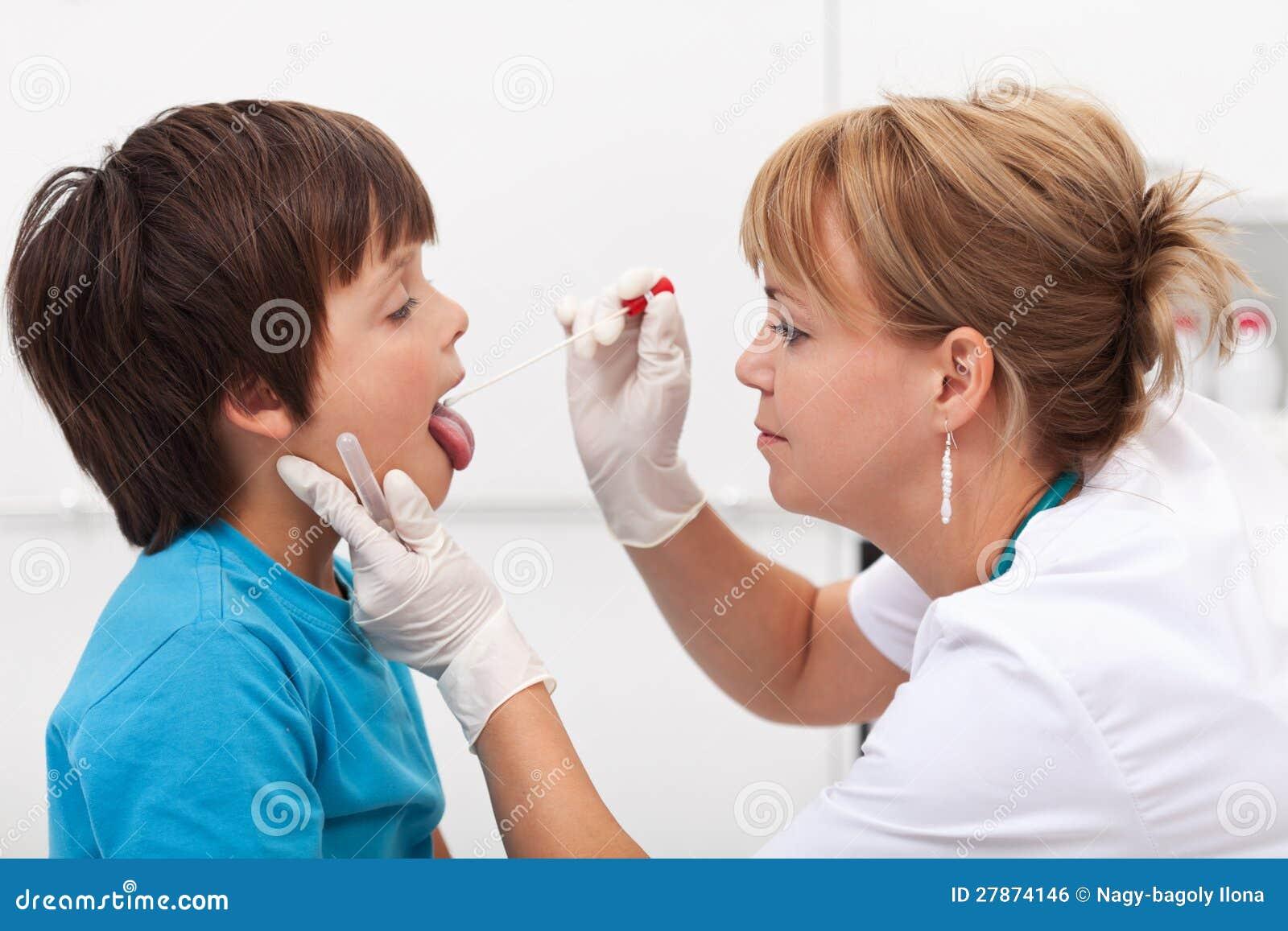 Hälsoprofessionell som tar salivaprövkopian från pojke