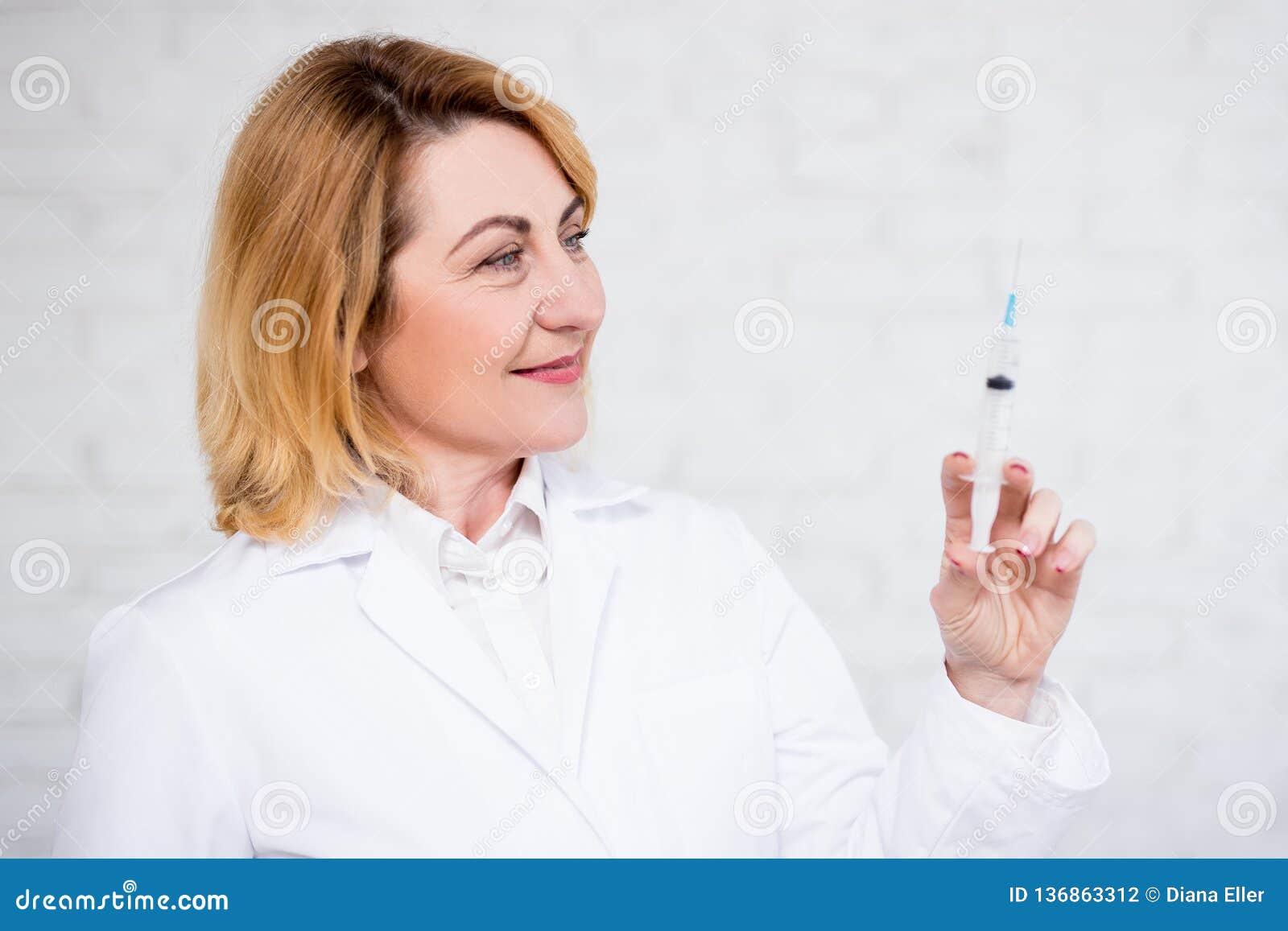 Hälsovård-, vaccinering- och cosmetologybegrepp - stående av den mogna kvinnliga doktorn som rymmer injektionssprutan över den vi