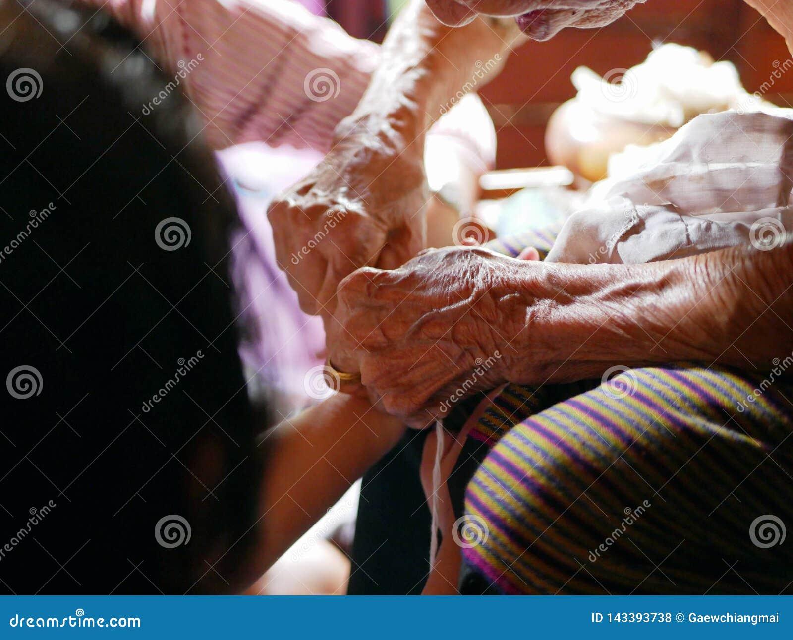 Hände der alten Frau ziehend, eine weiße Schnur Sai Sin nach der Bindung sie um ihre Enkelinhände wellenartig bewegend - thailänd