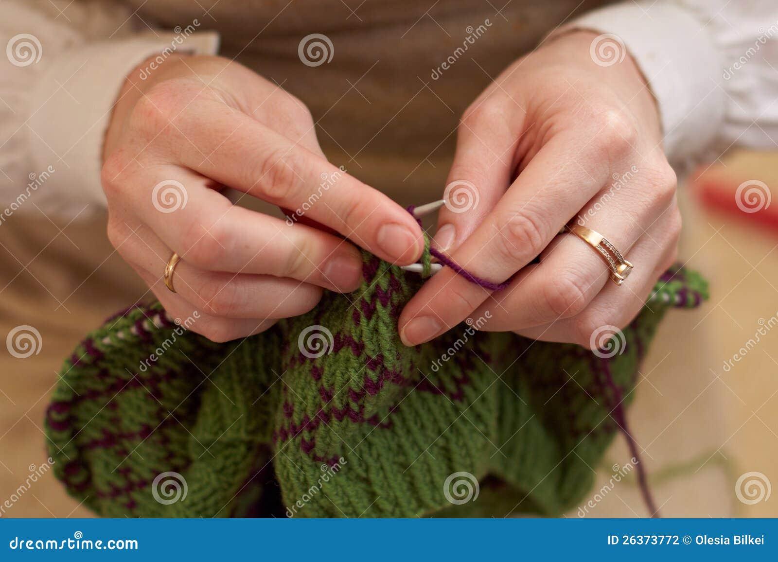 Hände der jungen Frau, die mit zwei farbigen Wollen stricken