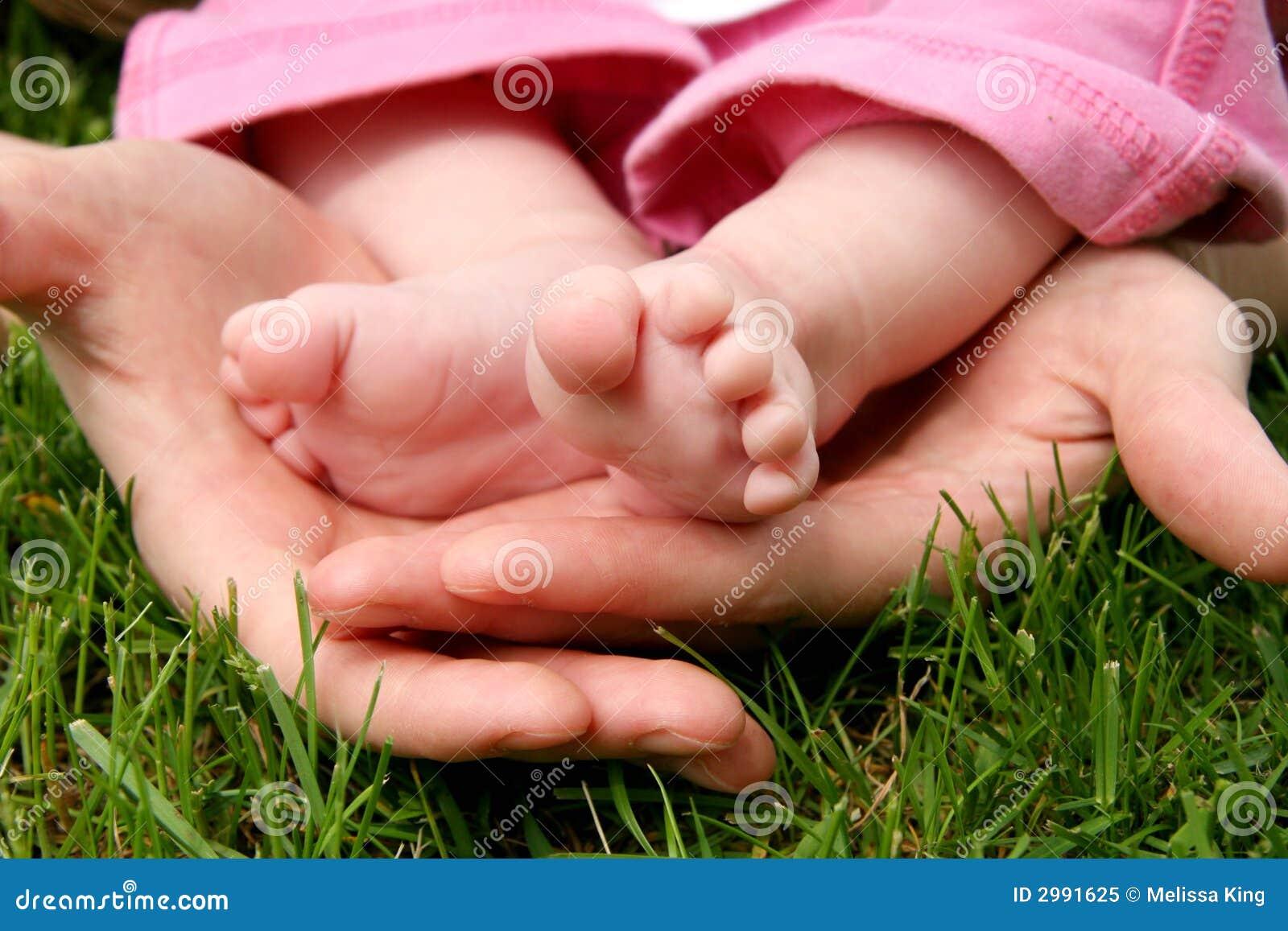 Hände des Mutter, die ihr Kind schaukeln