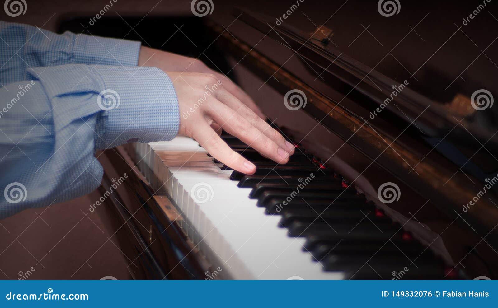 H?nde, die auf einem Klavier spielen