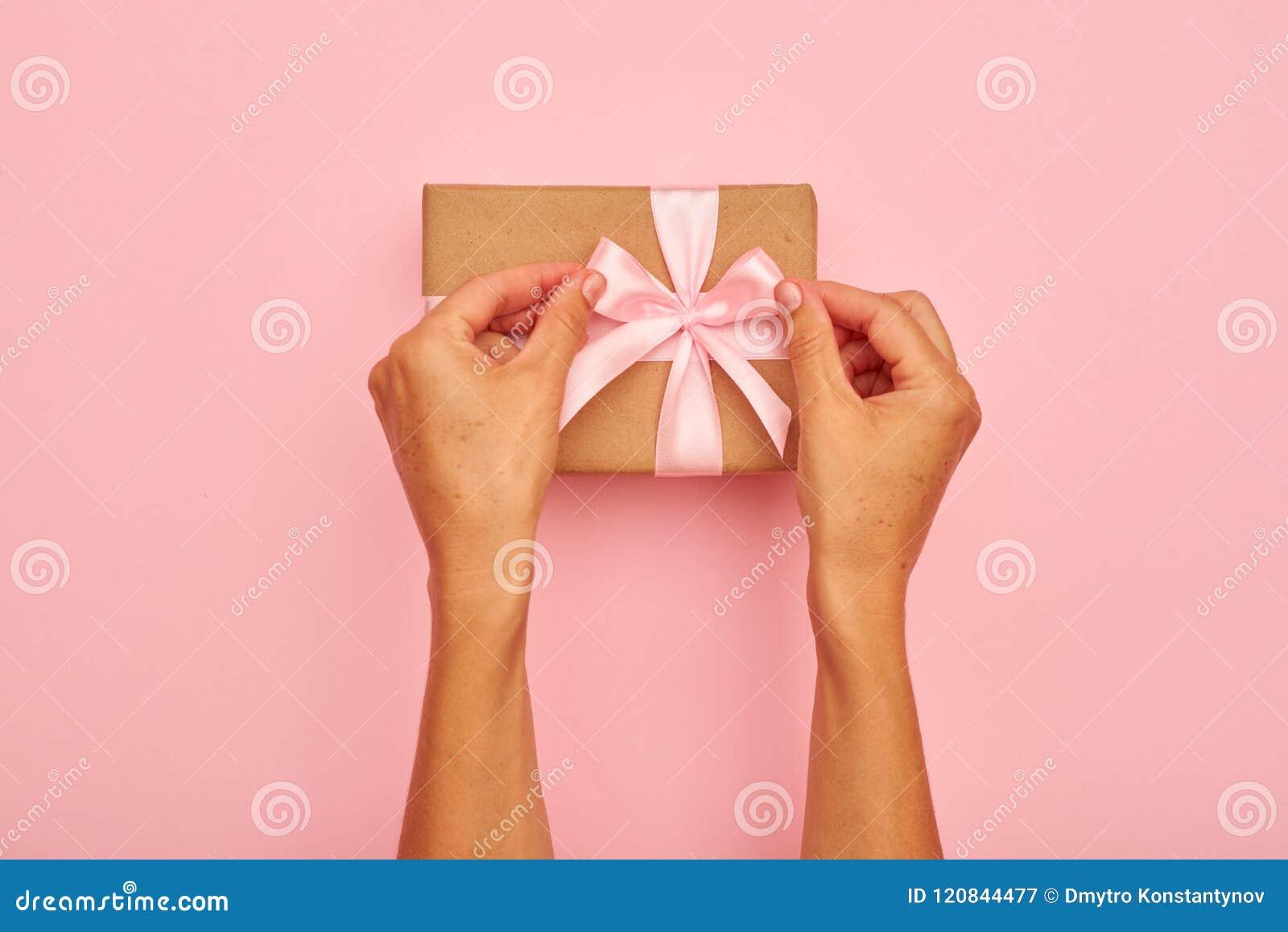 Hände, die rosa Bogen auf einem Präsentkarton binden