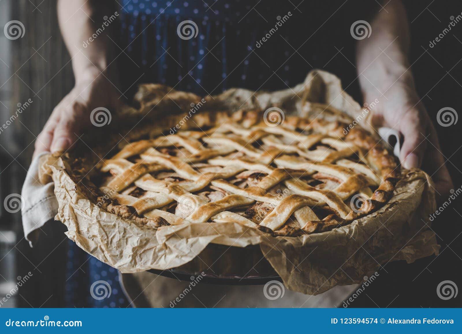 Hände, die selbst gemachten köstlichen Apfelkuchen halten Abschluss oben