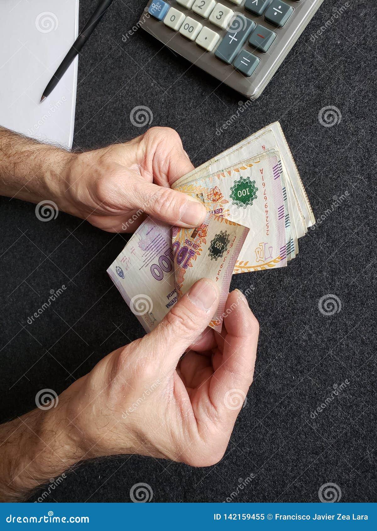Hände eines älteren Mannes, der Argentinien-Banknoten zählt