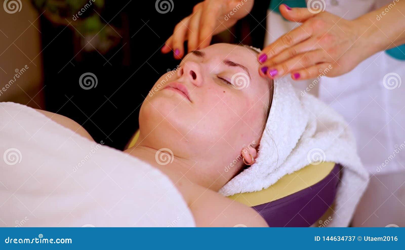 Hände eines Cosmetologist in einer Kreisbewegungsmassage die Backen, die Augenbrauen und die Stirn Die Kundenlügen entspannt auf stock footage