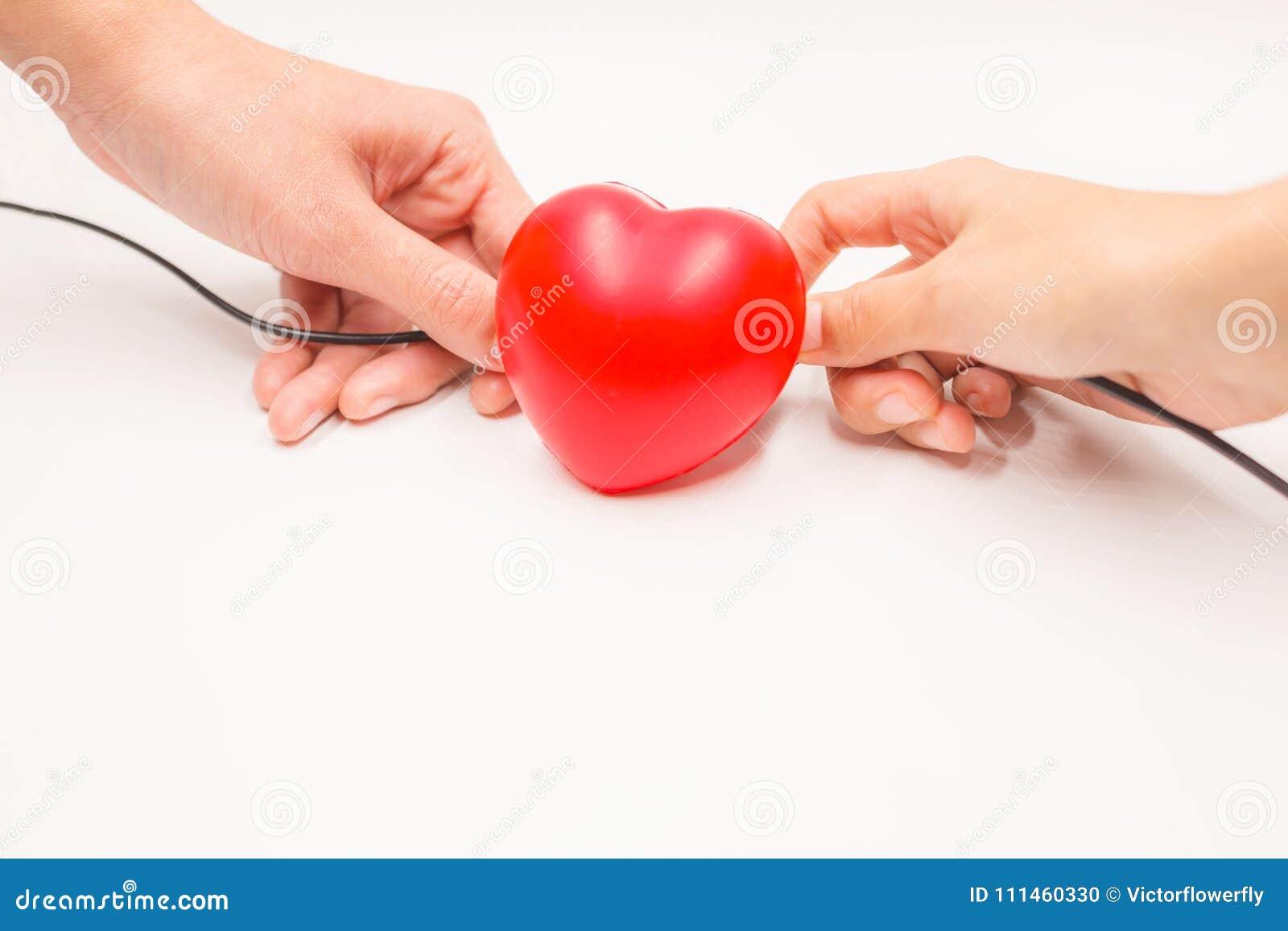Hände mit der Aufladung verkabelt, um Herz, auf weißem Hintergrund wieder herzustellen zu helfen Herzkrankheitsschutz, proaktive