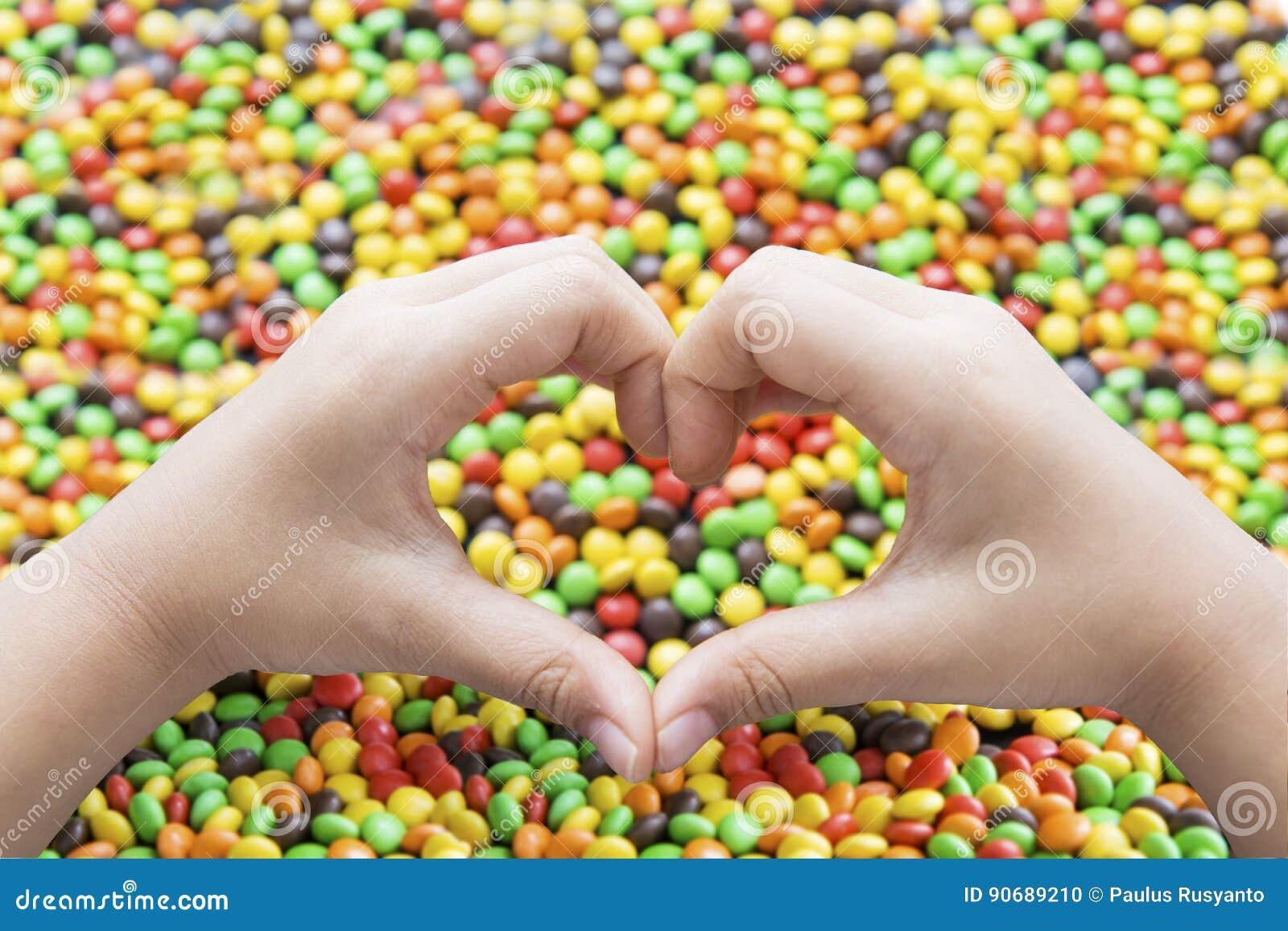 Hände mit Herzsymbol und bunten Süßigkeiten