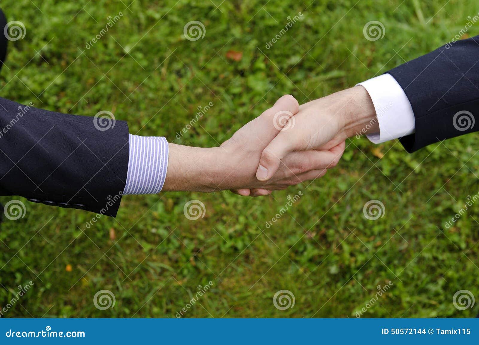 Händedruck von zwei Geschäftsmännern in den Klagen