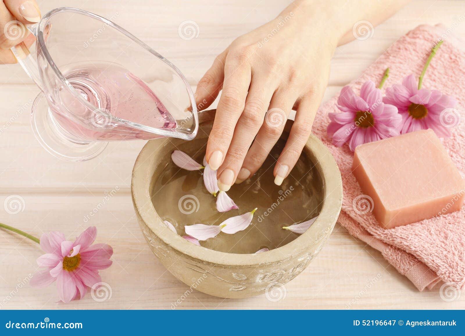 Händer över den keramiska bunken med vatten och nödvändiga oljor