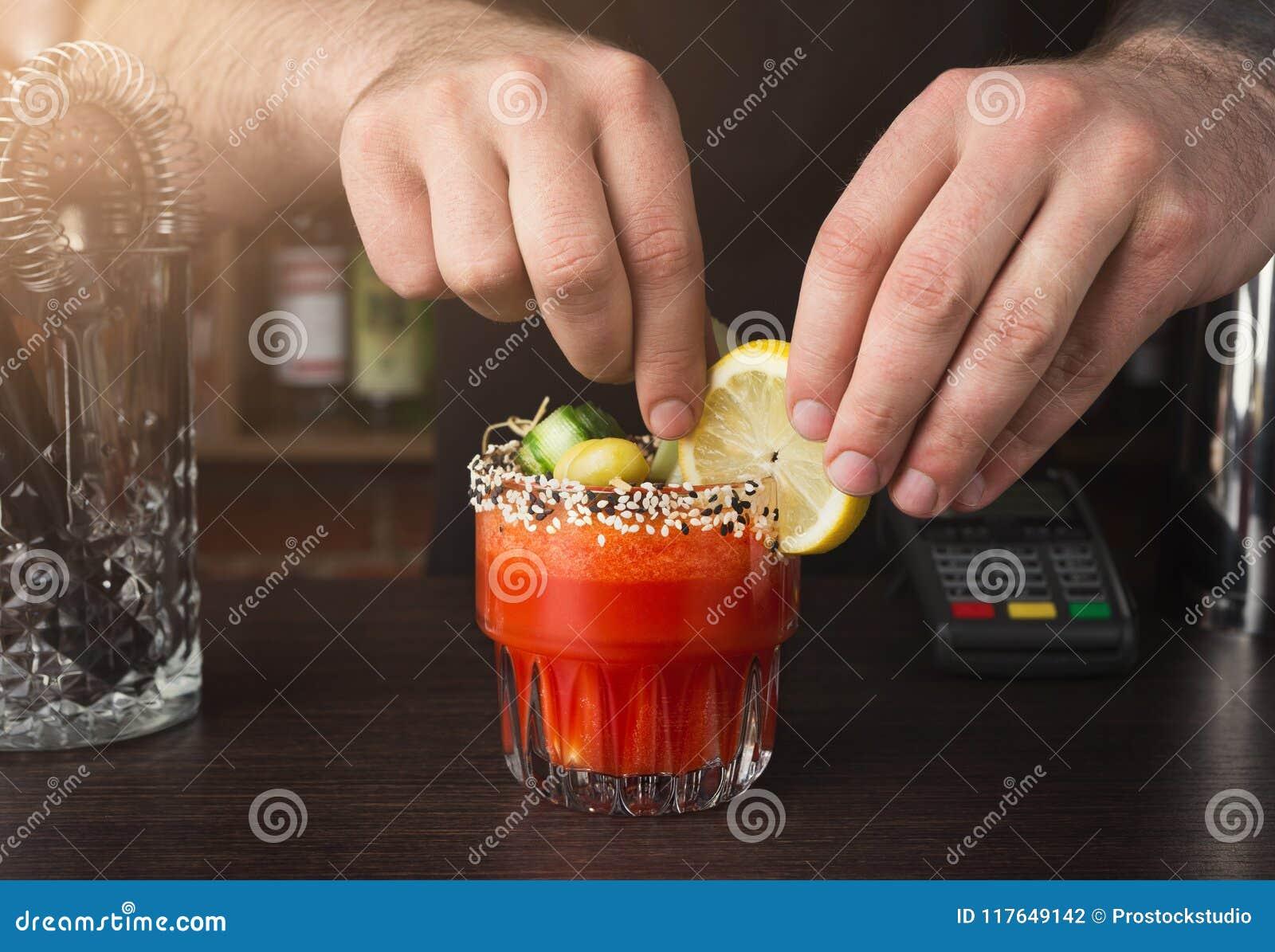 Händer av bartendern som förbereder coctailen på stångräknaren