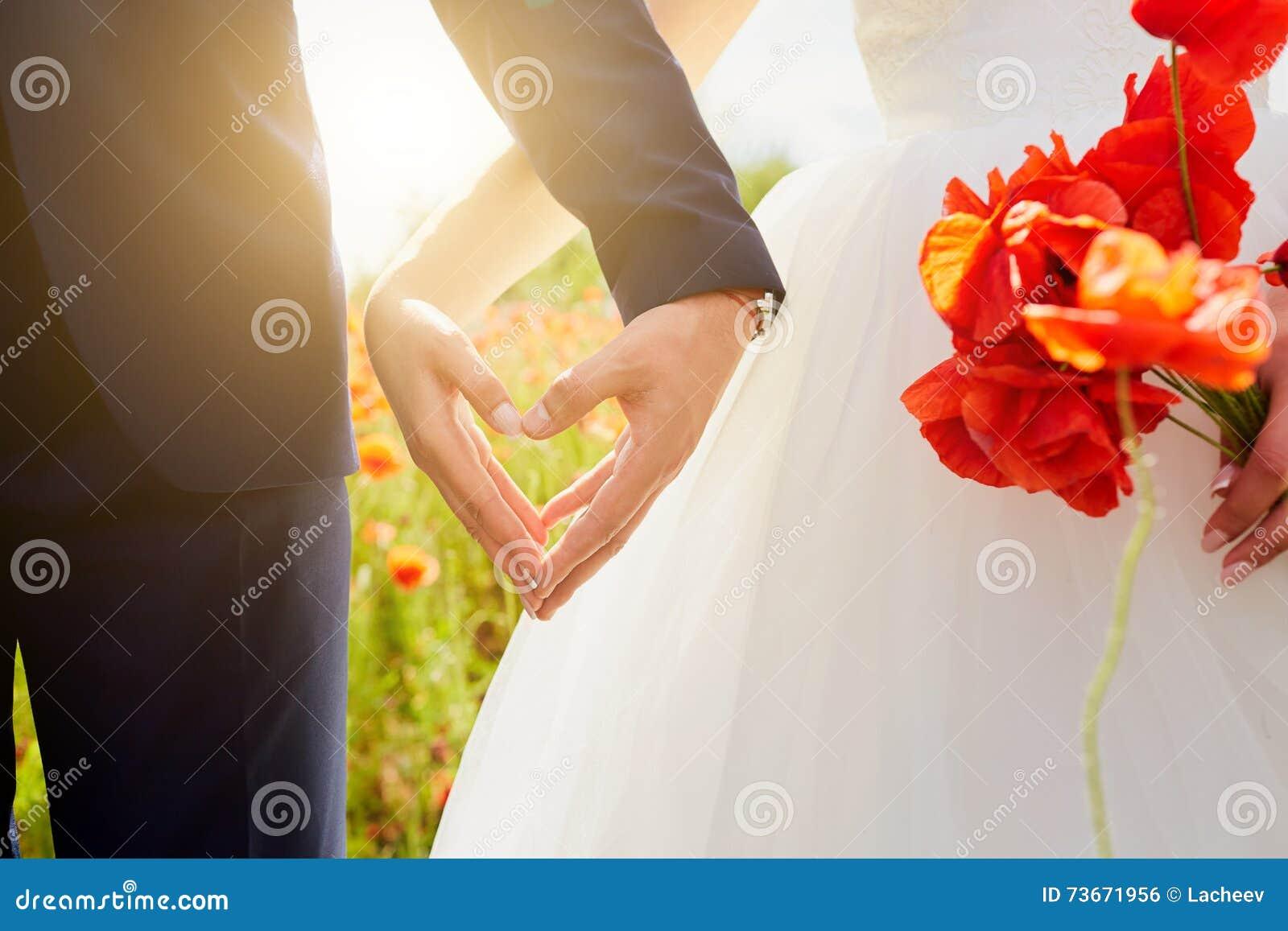 Händer av bruden och brudgummen i en form av hjärta Att gifta sig förälskelse, hör