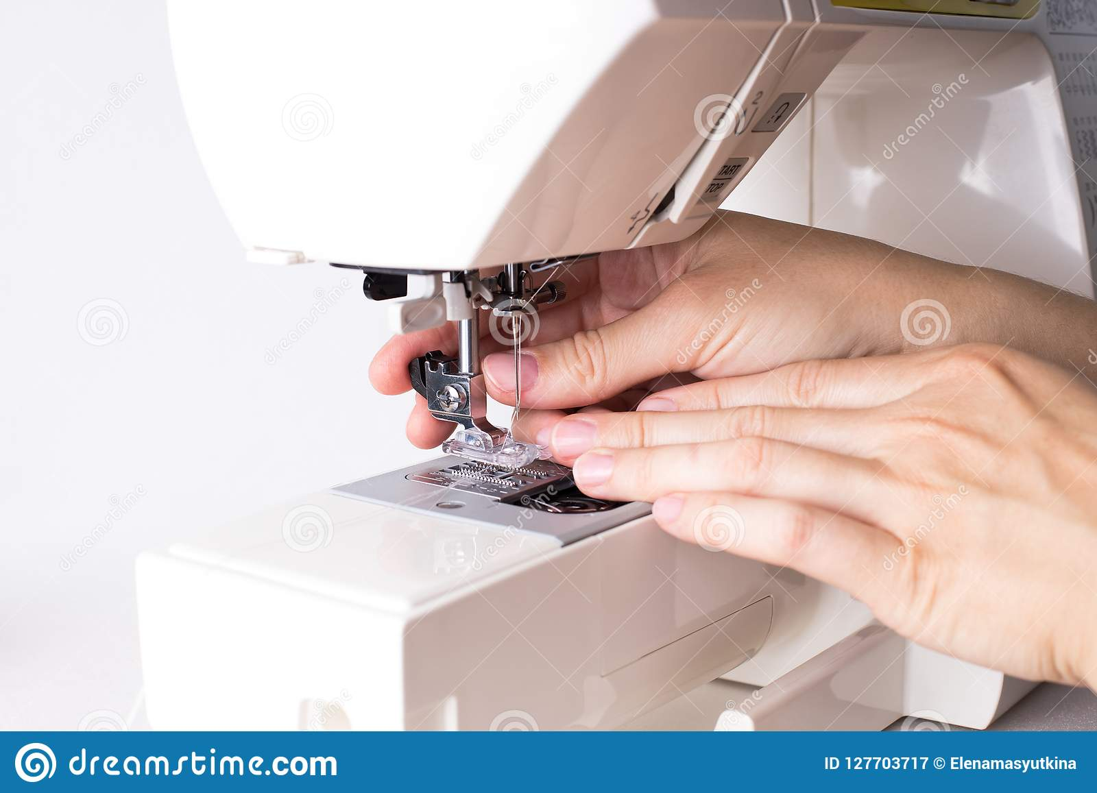 Händer av den kvinnliga fixa foten av symaskinen