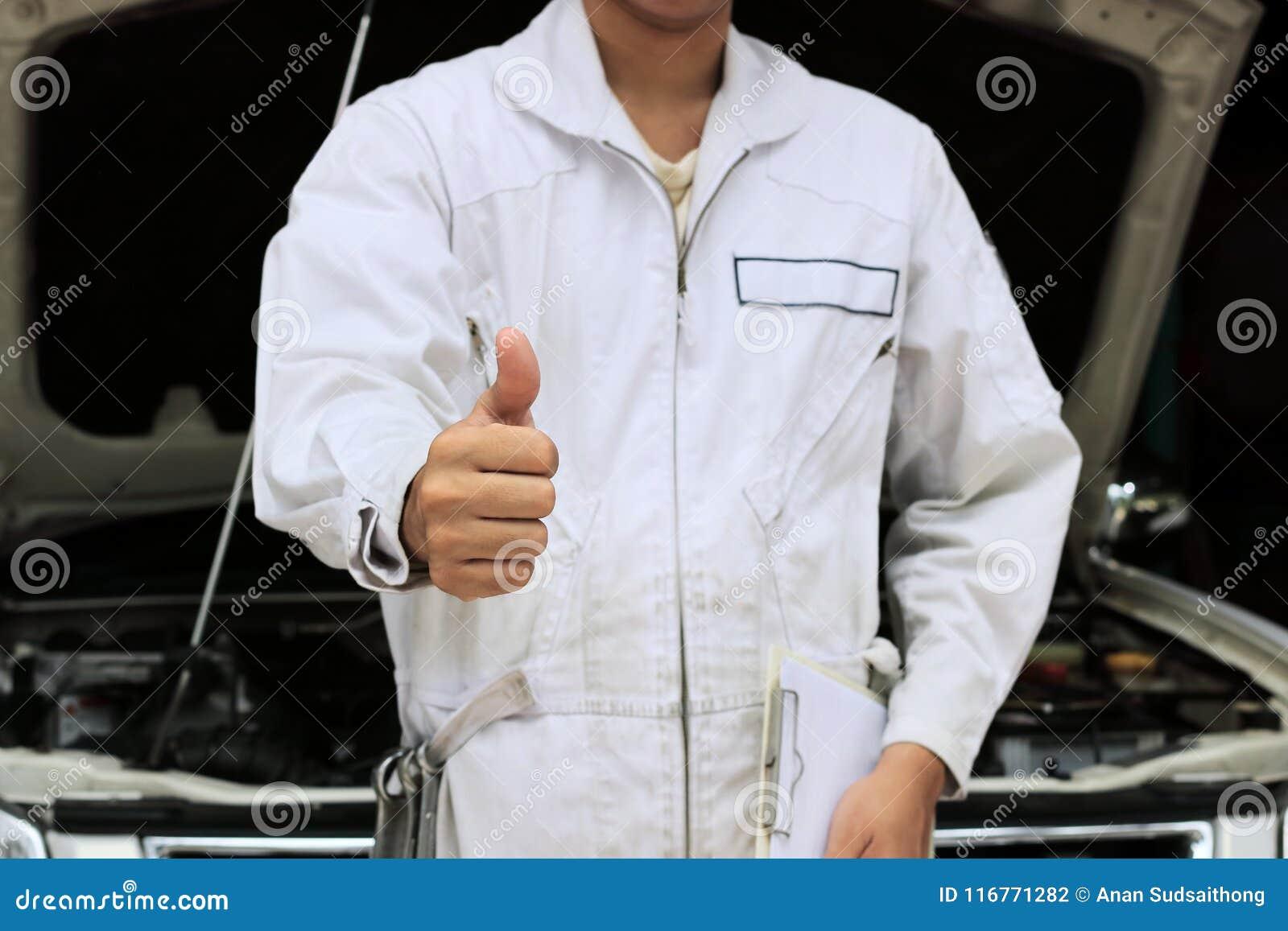 Händer av den yrkesmässiga unga mekanikermanvisningen tummar upp som tecken av framgång med bilen i öppen huv på garagebakgrunden