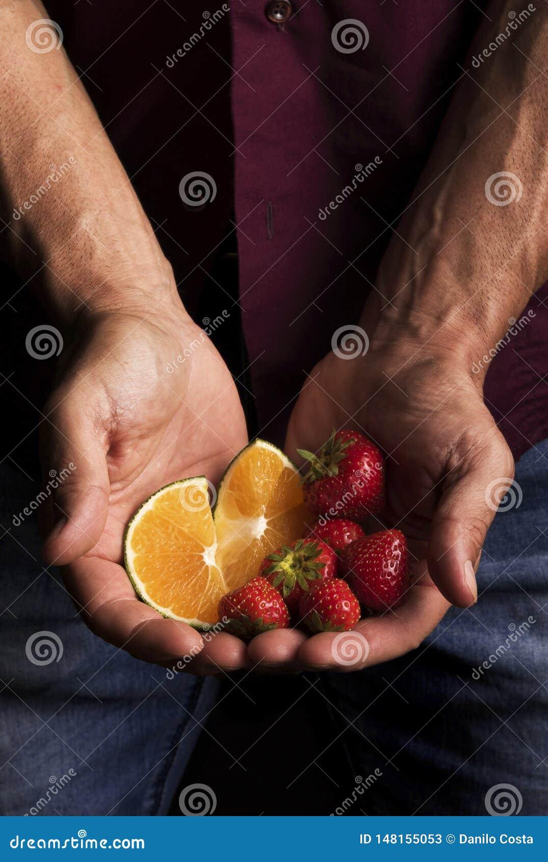 Händer av en man som rymmer frukt