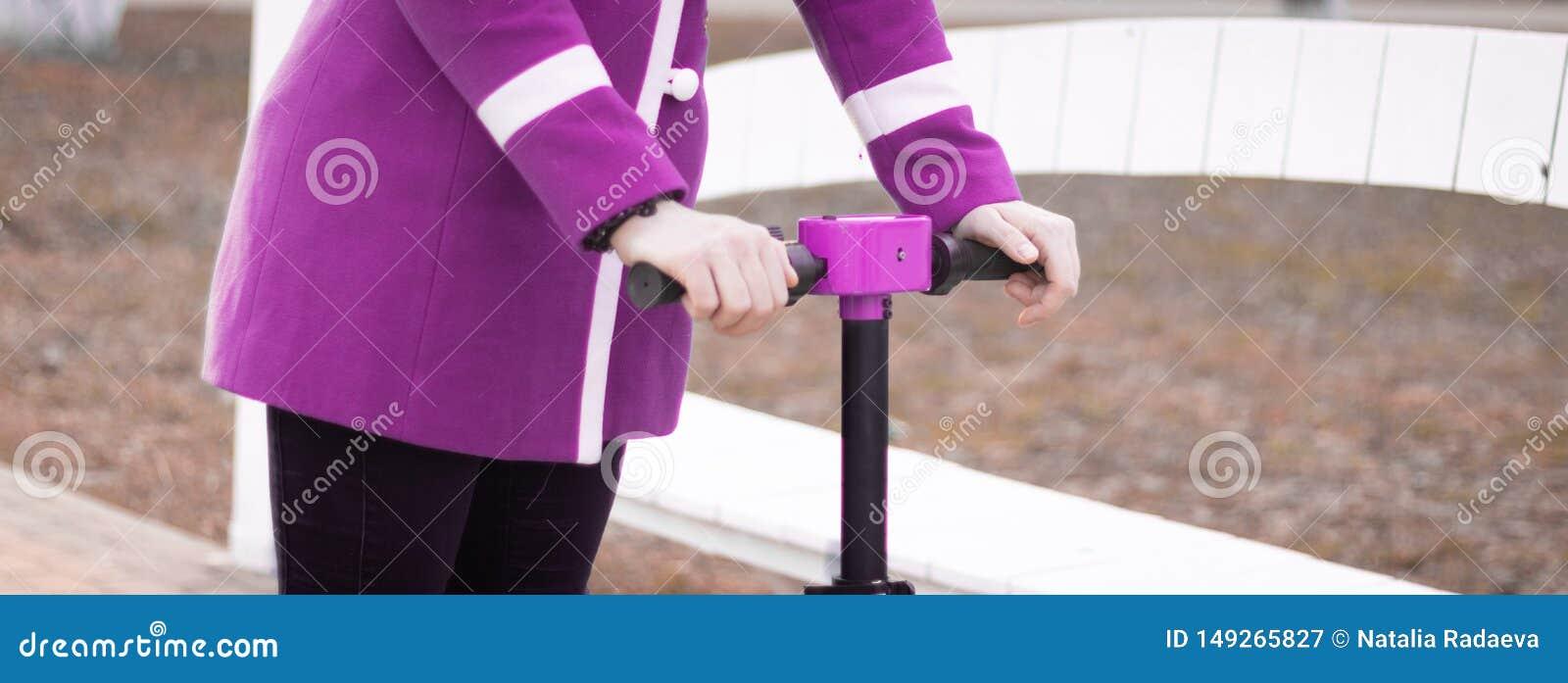 H?nder av en ung kvinna som rymmer styrhjulet av en elektrisk sparkcykel Synligt rosa - purpurf?rgat lag Ingen framsida panorama