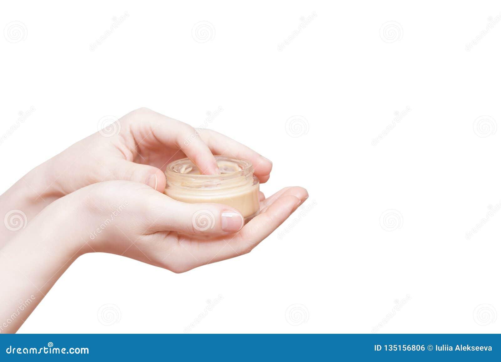 Händer av flickan med en krus av slut för framsidakräm upp vit isolat