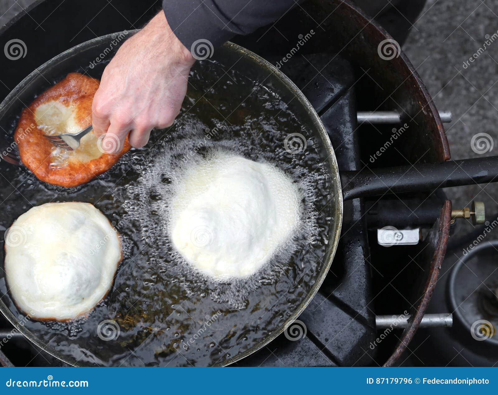 Händer av kocken som steker stor frybread i en panna av varm olja