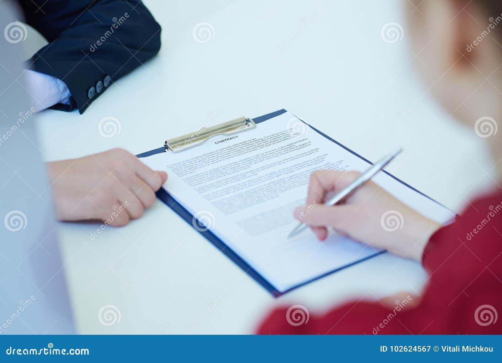 Händer av kvinnan som undertecknar avtalet Selektivt fokusera