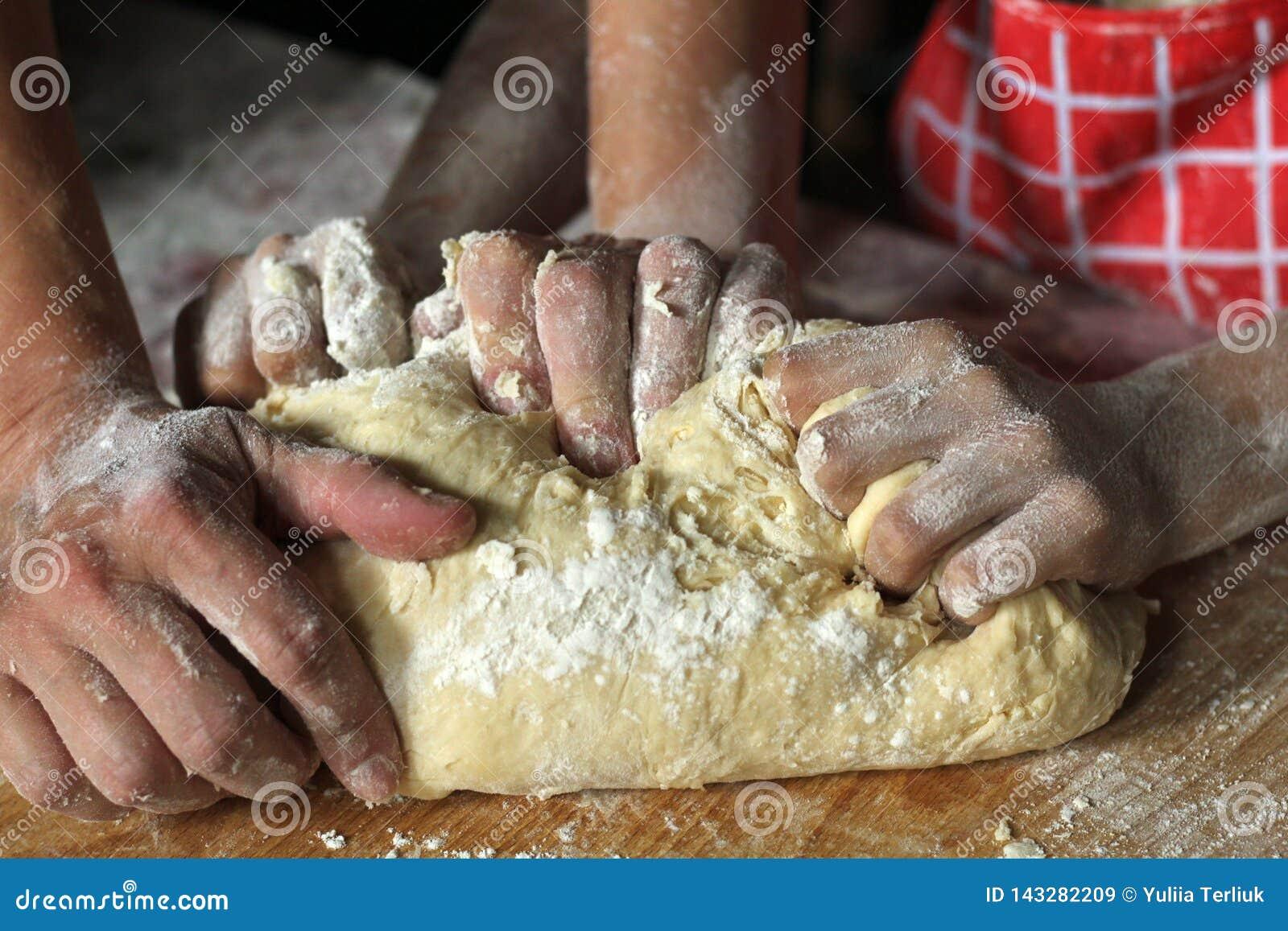 Händer av modern och dottern som tillsammans knådar deg i köket