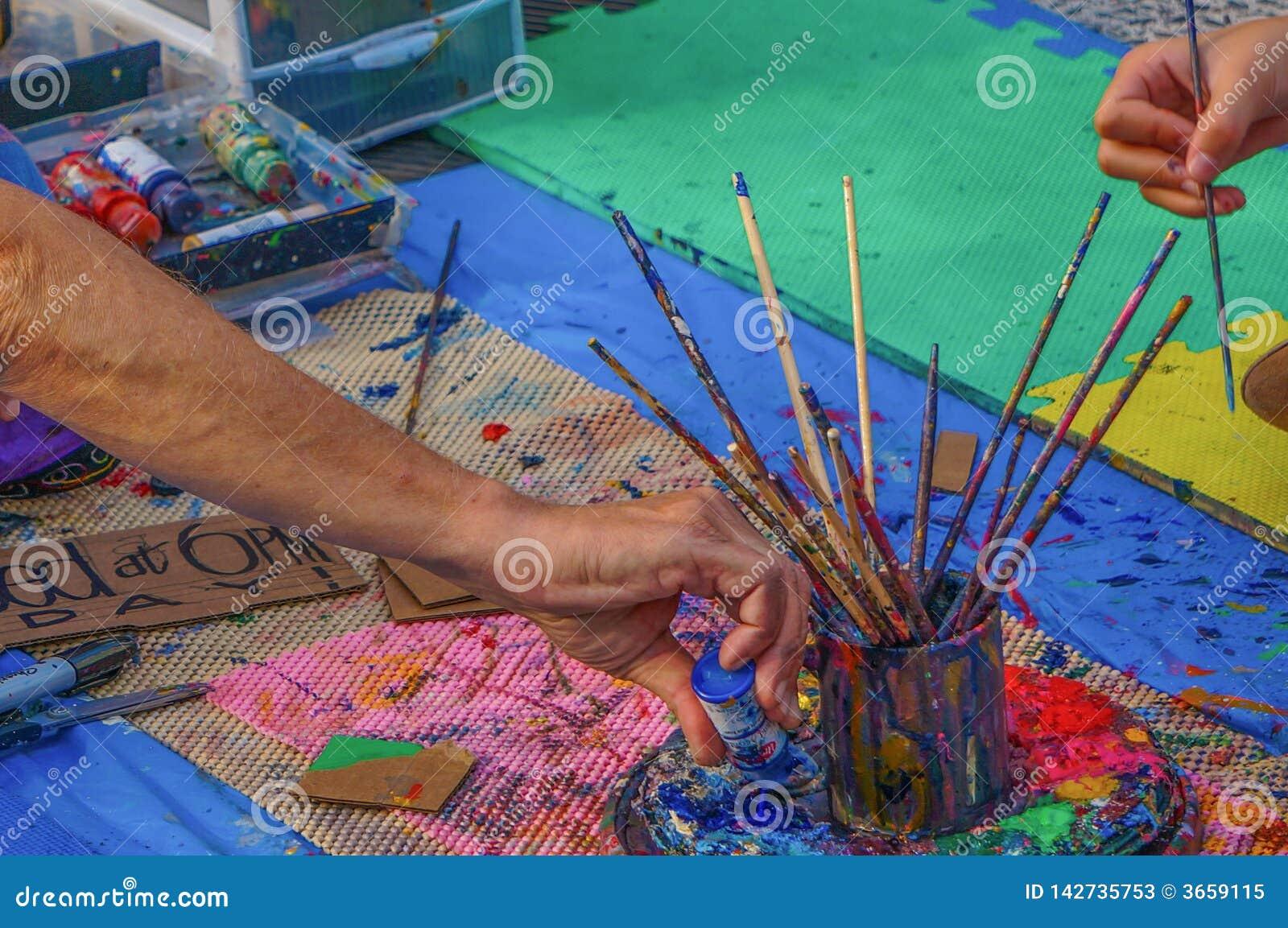 Händer av två olika personer som konstnärer nära tefatet med rånar av borstar på mattan, häller flaskan av blå målarfärg, hållbor