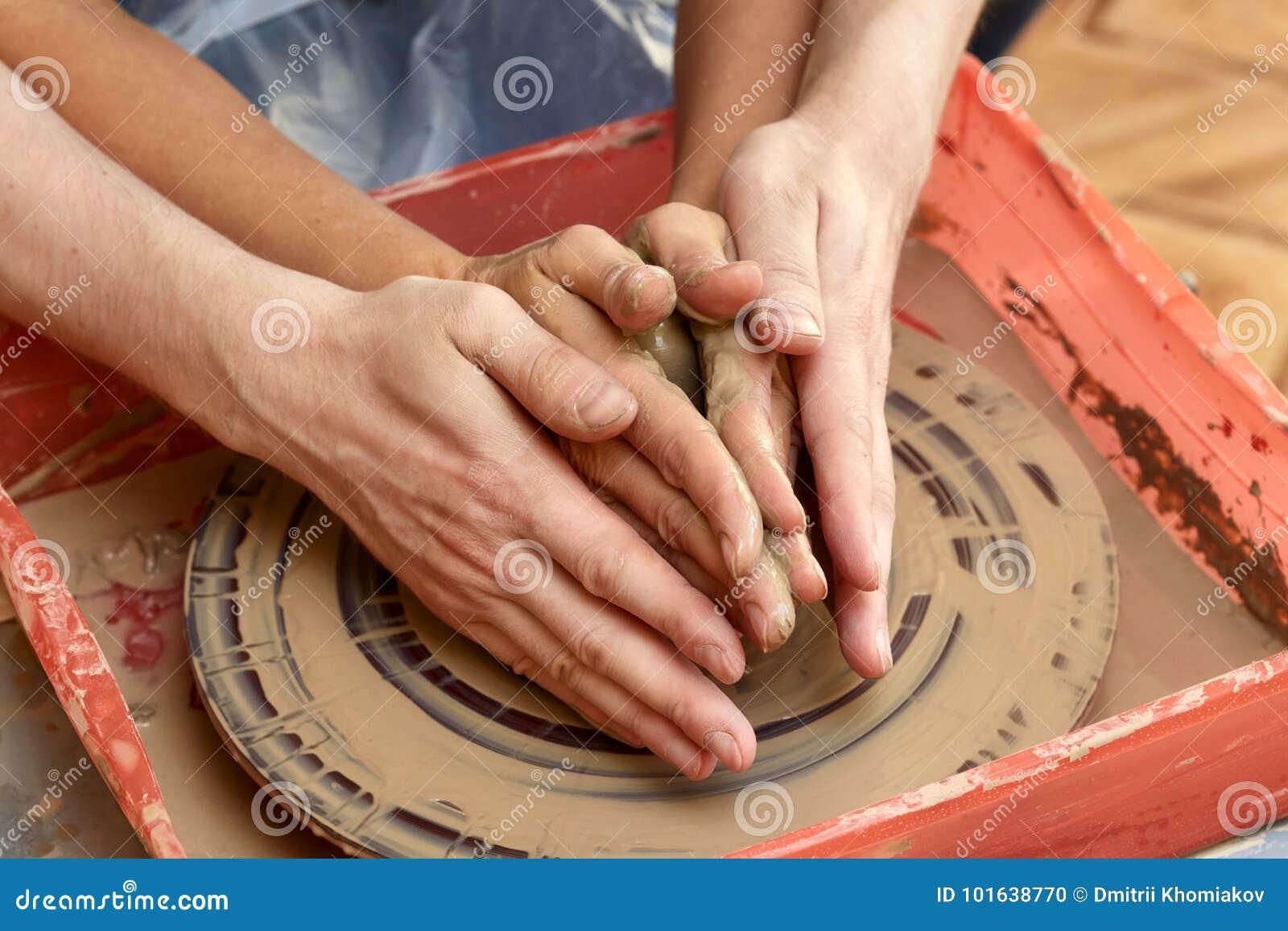 Händer av två personer skapar krukan, hjul för keramiker` s Undervisningkrukmakeri