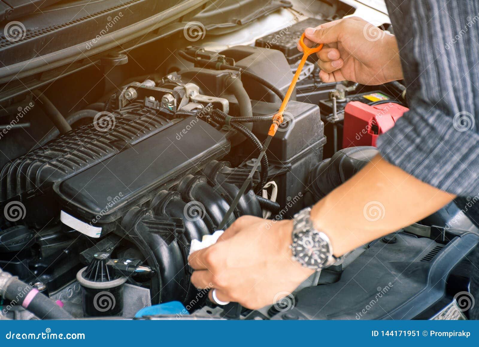 Händer för arbetare för för man som eller automatisk mekaniker kontrollerar det bilmotoroljan och underhållet