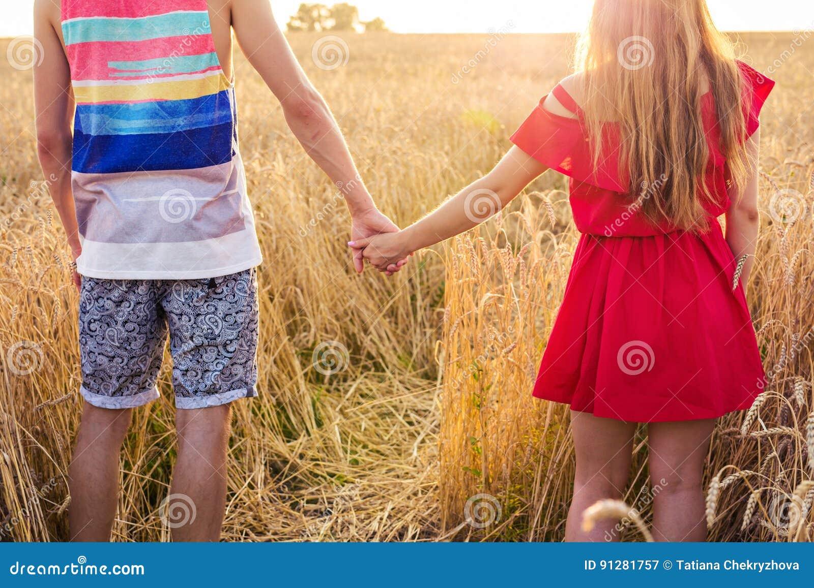 Händer för barnparinnehav i vetefältet på den soliga sommardagen, baksidasiktsnärbild