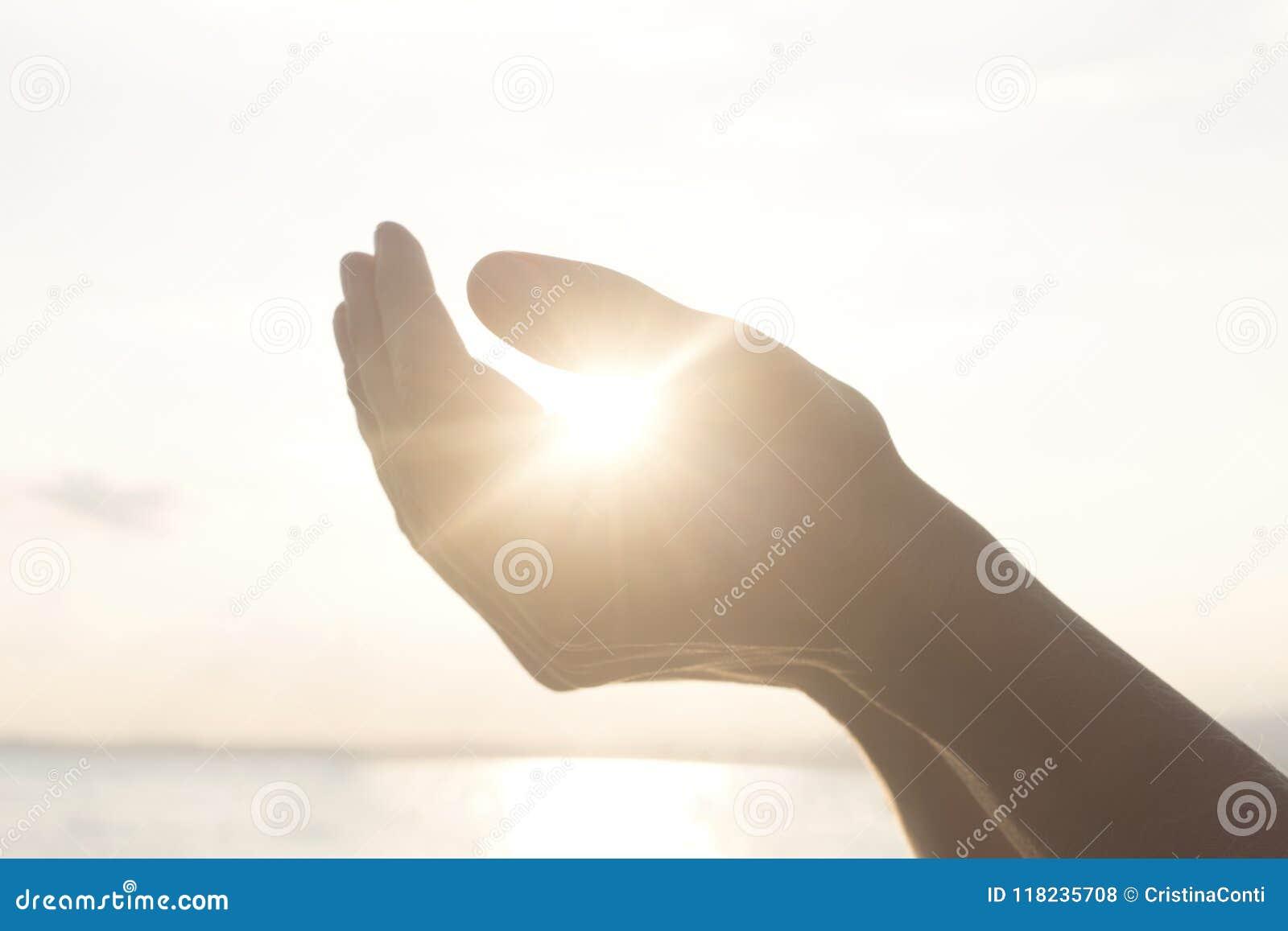 Händer för kvinna` s rymmer solen och dess energi