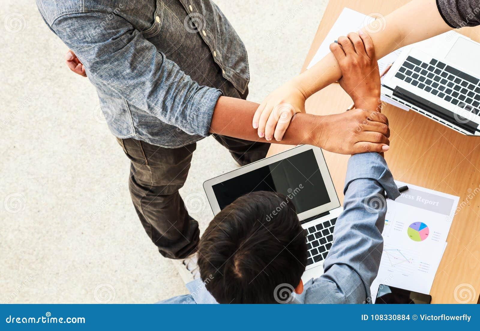 Händer för möte för teamwork för affärsfolk sammanfogande i triangel i kontorsbegreppet, genom att använda idéer, diagram, datore