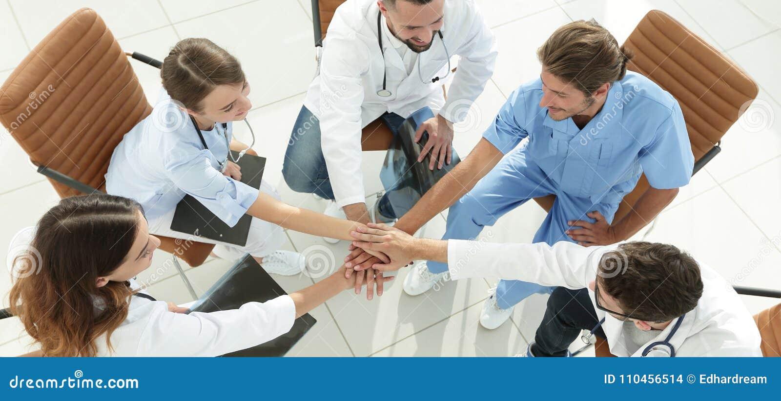 Händer för medicinsk personal som tillsammans knäppas fast och att sitta på ett skrivbord
