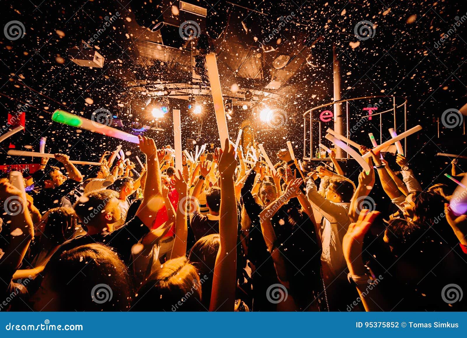 Händer för nattklubbkonturfolkmassa på konfettier ångar upp etappen