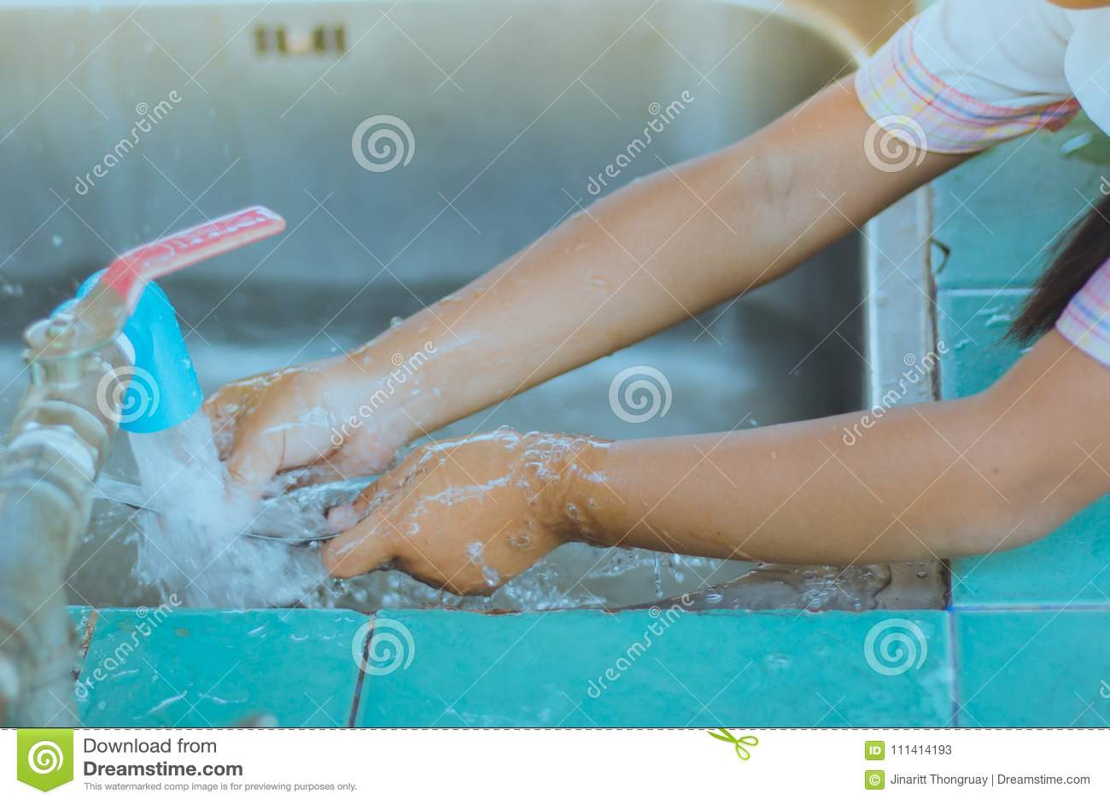 Händer för slut av dagisstudenten gör upp till ren en sked