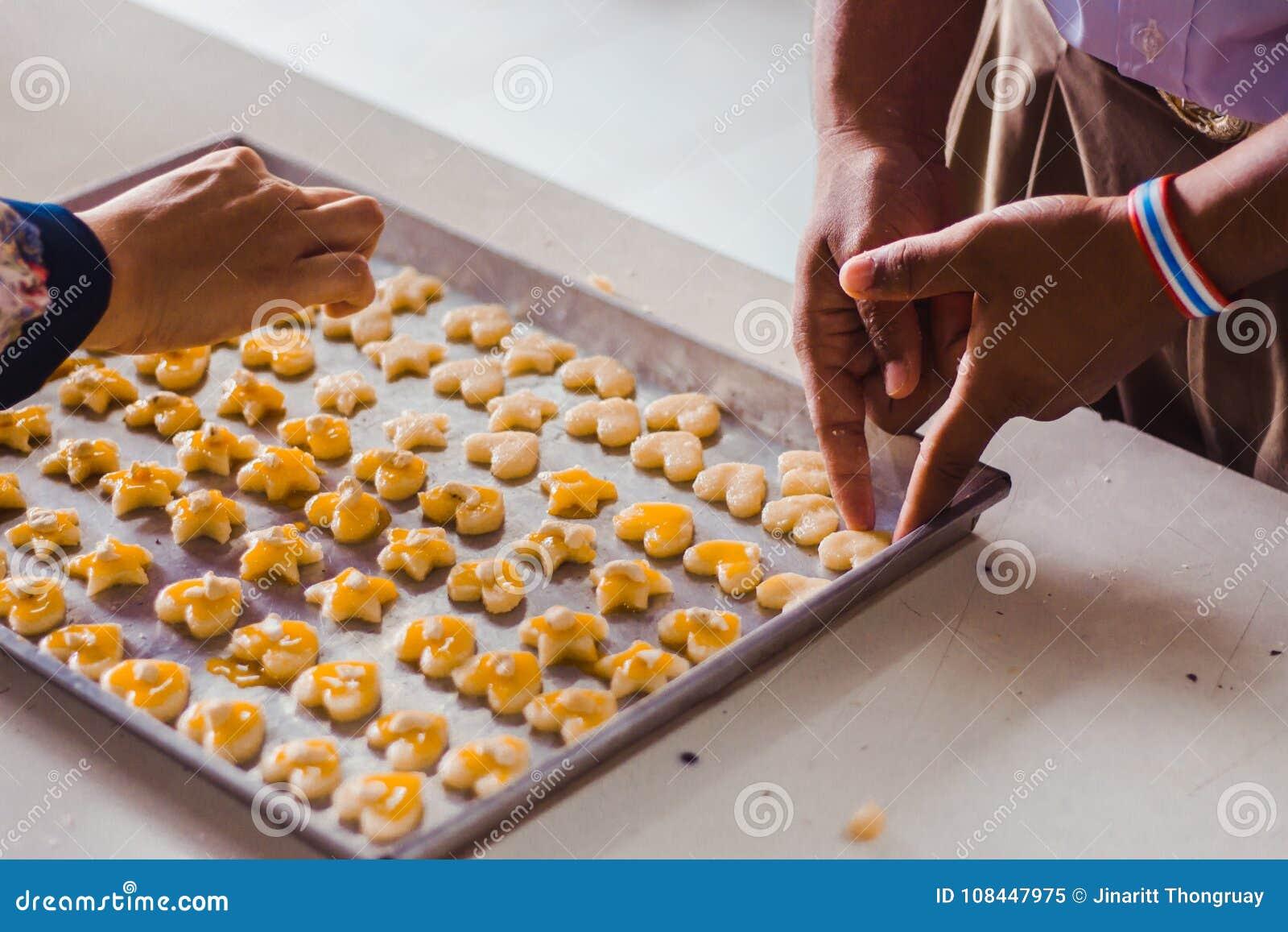 Händer för student` s gör Singapore kakor från deg i skola