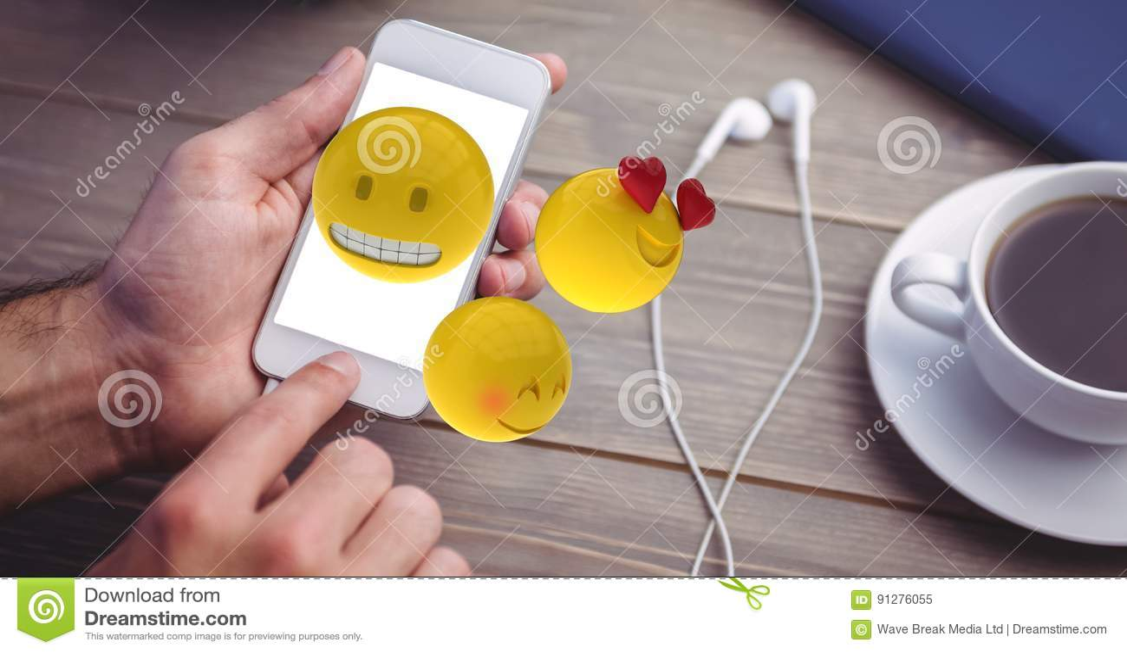 Händer genom att använda emojis på den smarta telefonen vid hörlurar och kaffekoppen på tabellen