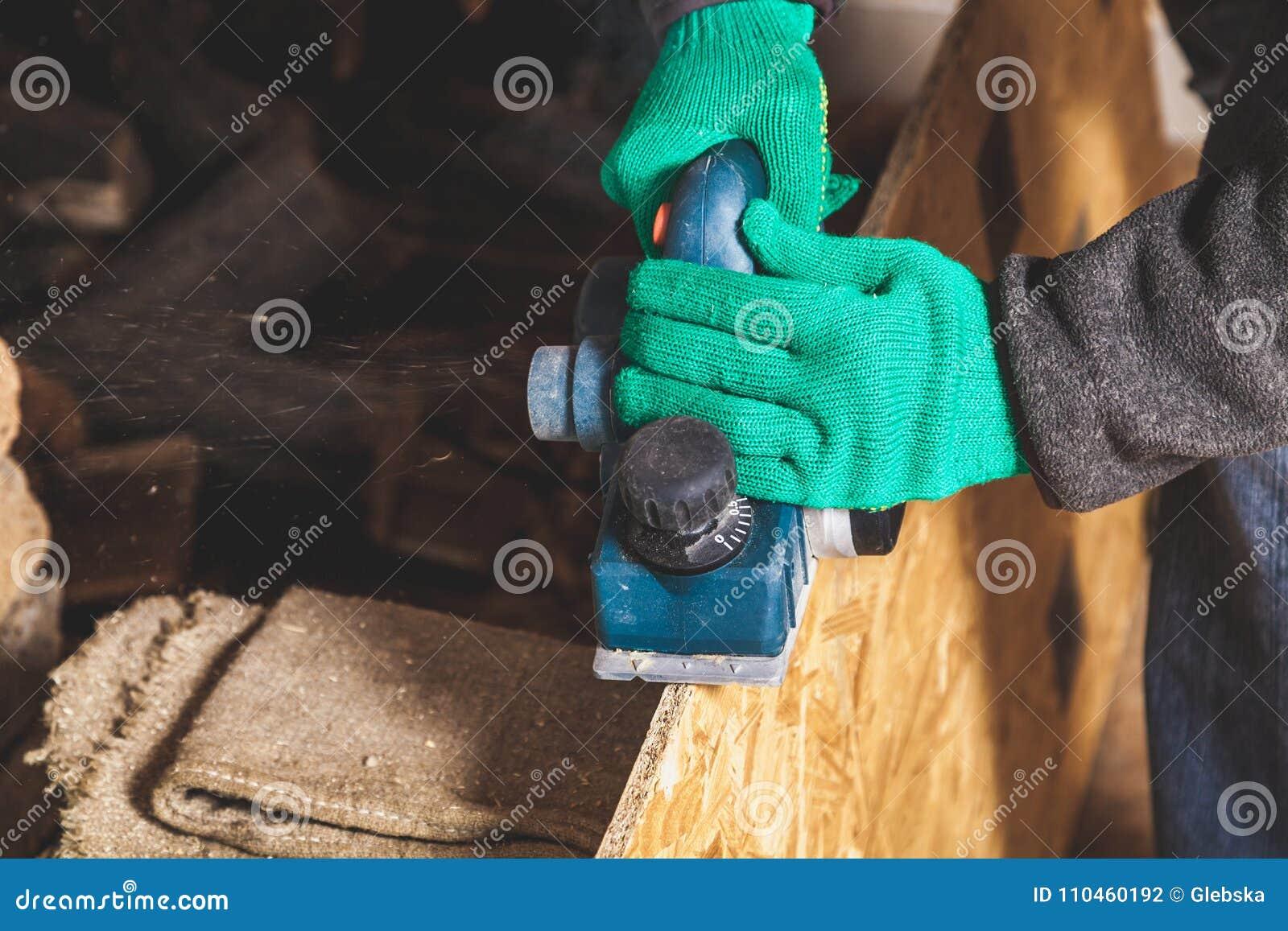 Händer i handskar planerar den wood plattan med en elkraftnivå