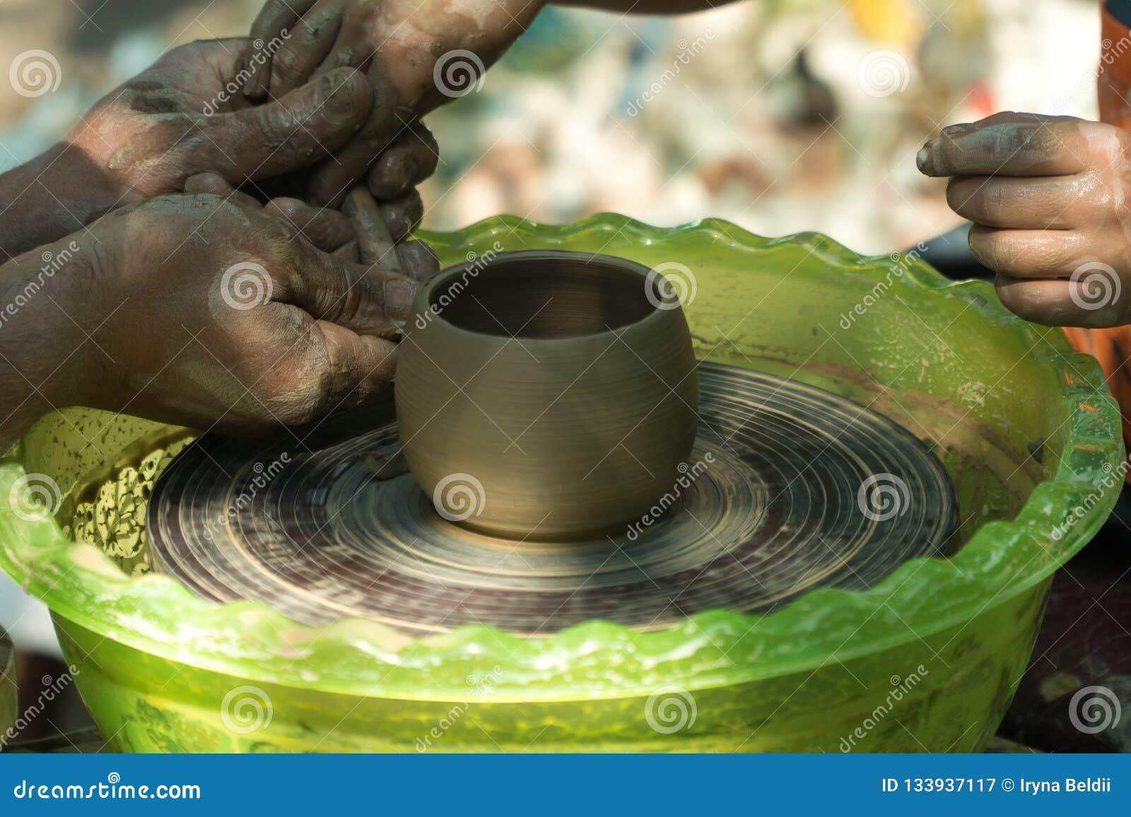 Händer i lera Keramikers hjul som gör en kopp av lera