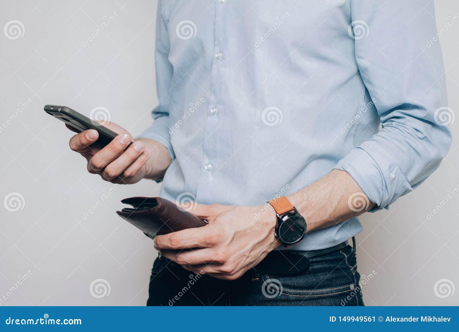 Händer med den bruna plånboken och telefonen