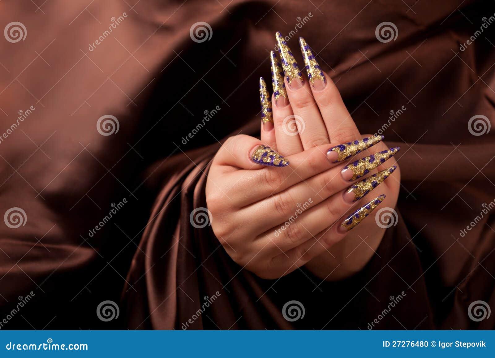 Händer med den långa fingernailen och den härliga manicuren