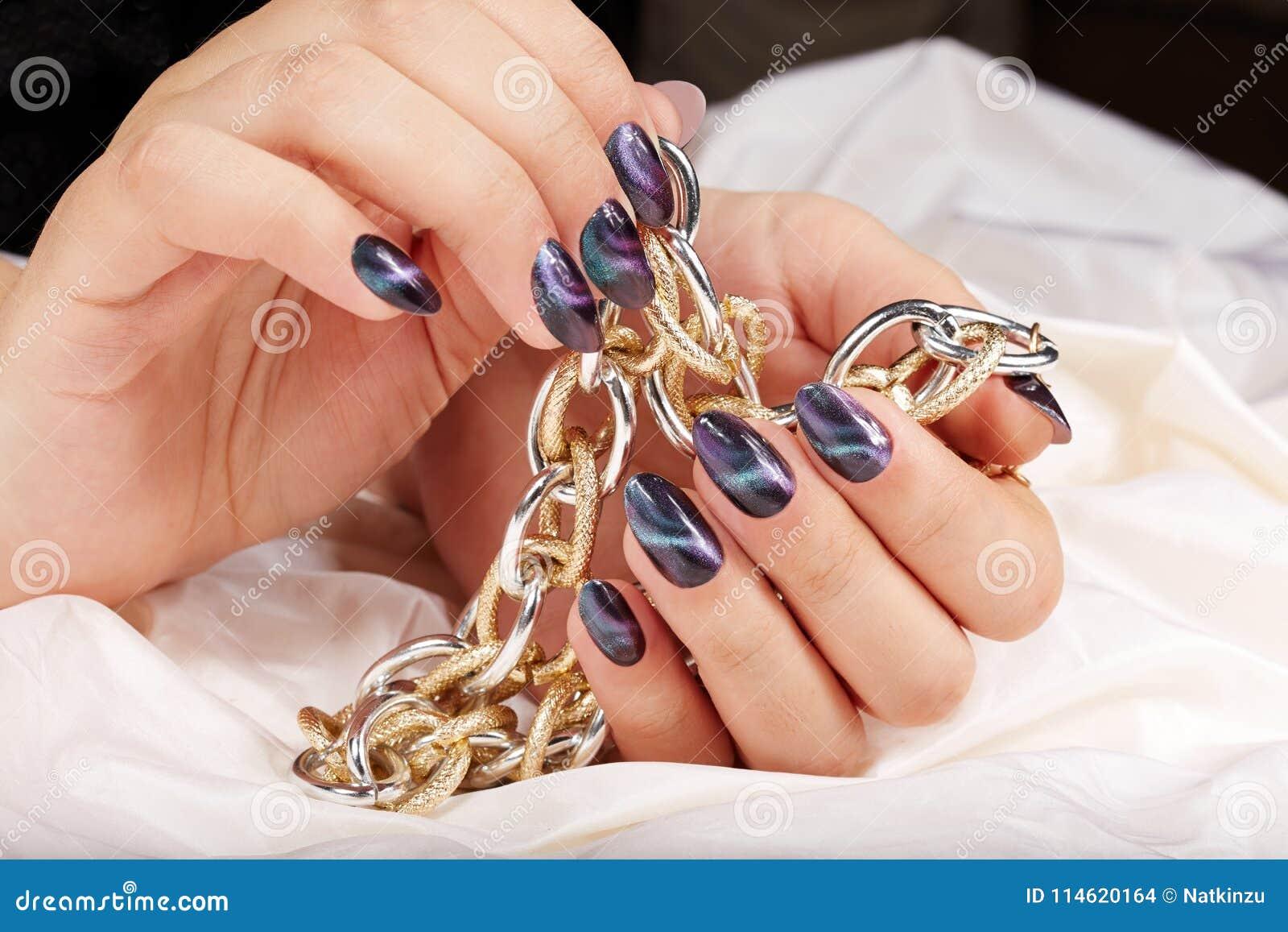 Händer med manicured spikar med designen för kattögat som rymmer en halsband